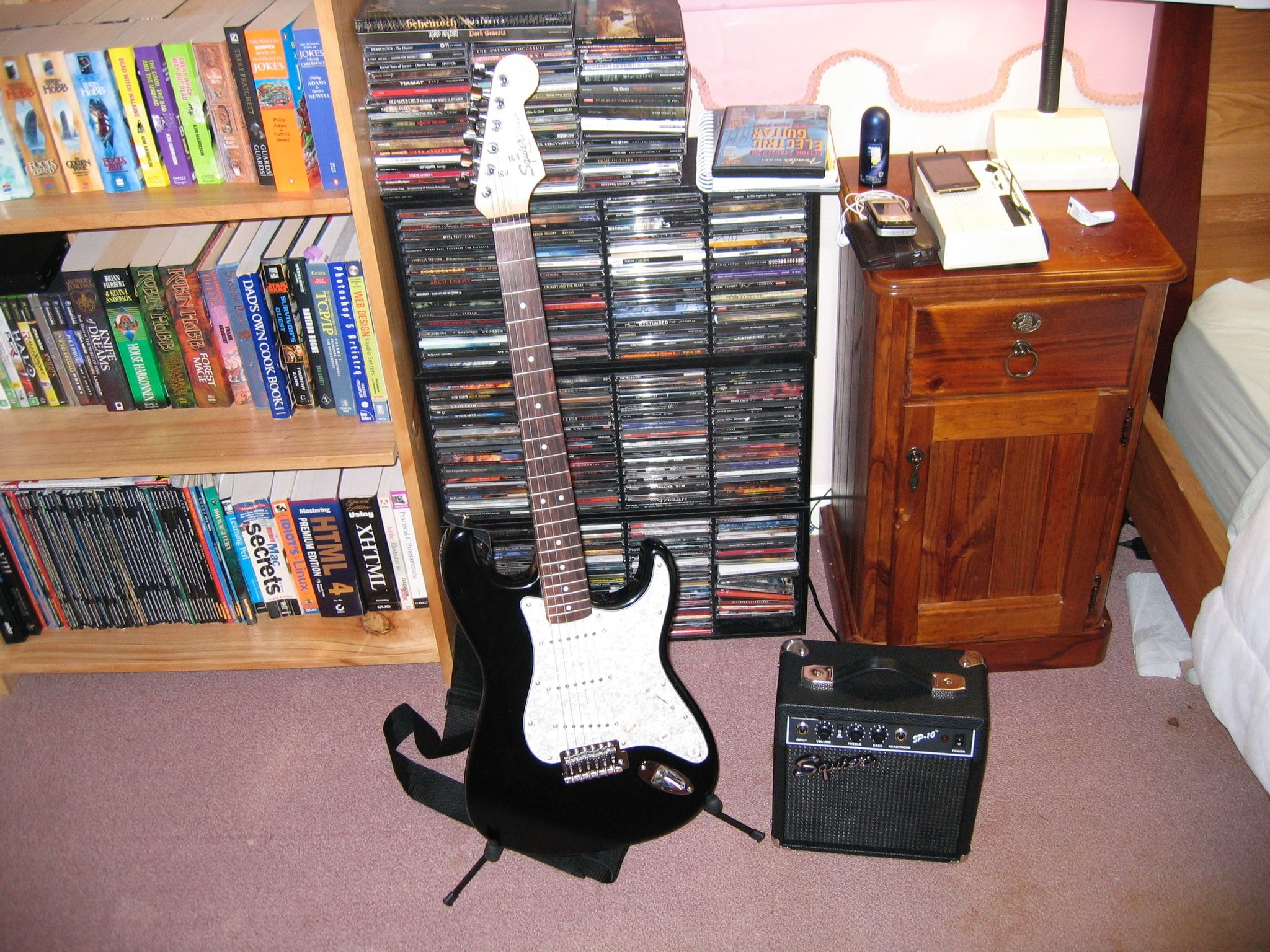 A photo of a black electric guitar with white scratch plate sitting on a guitar stand, next to a teensy little amp.