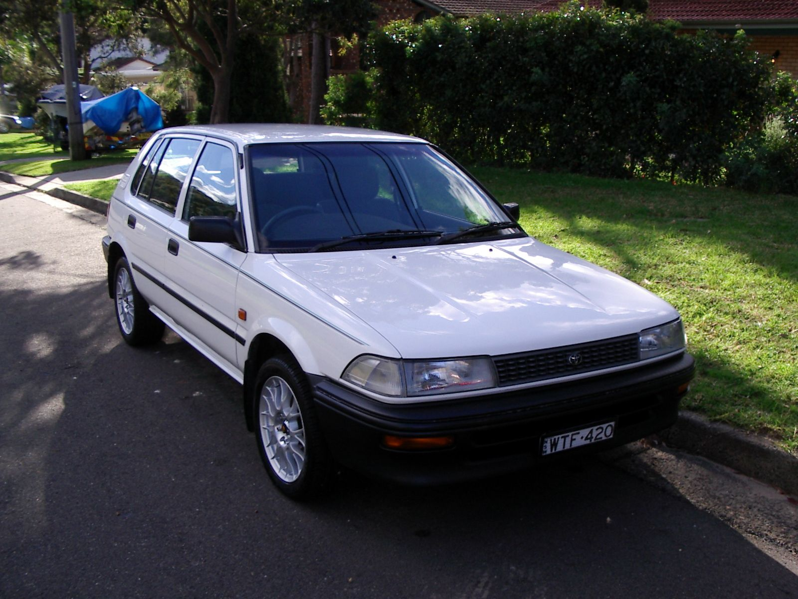 "A photo of a white 1993 Toyota Corolla hatchback with low-profile tyres, lace-style rims, and numberplates that say ""WTF420"". It's very shiny and clean-looking."