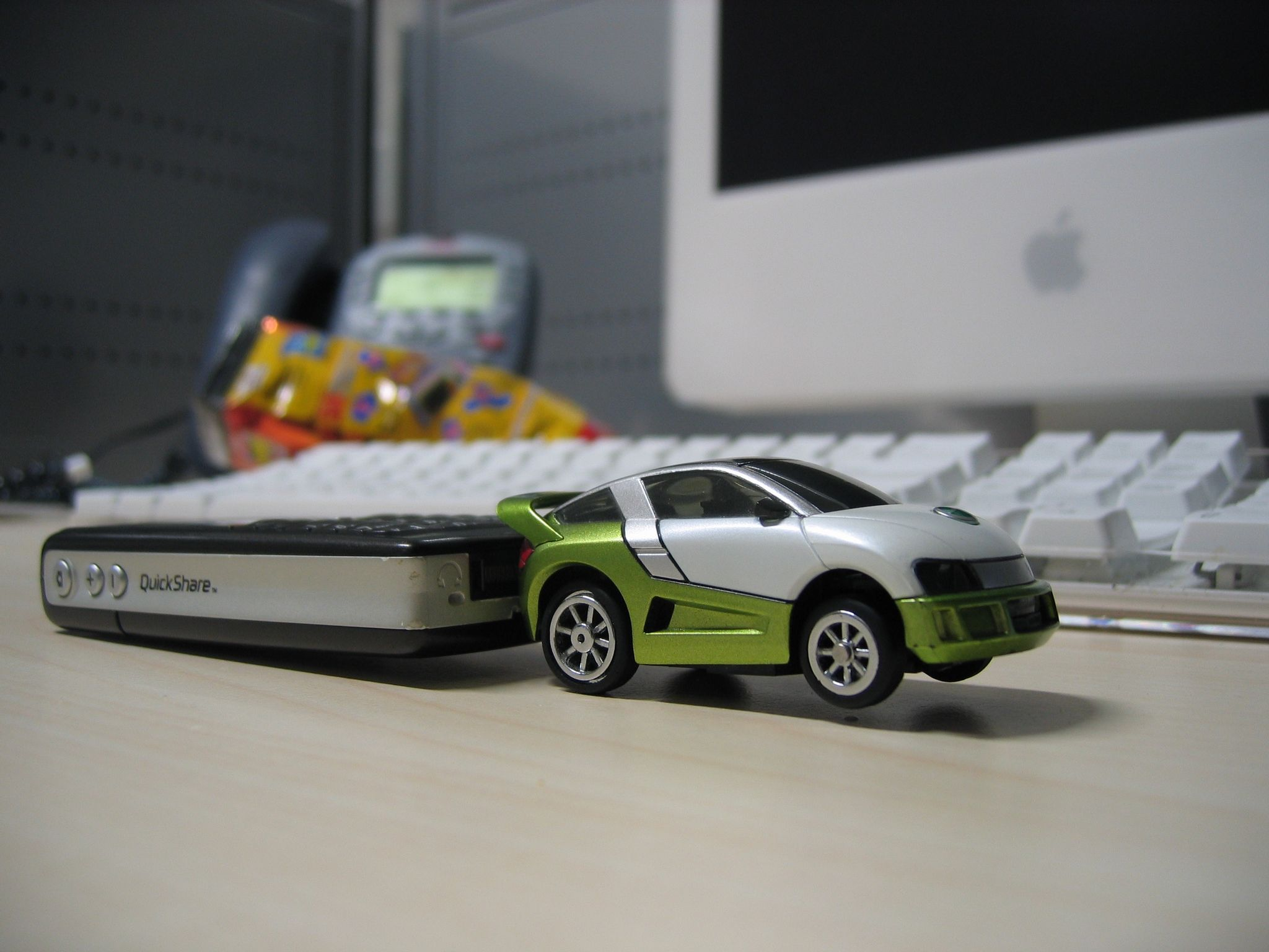 A tiny green and white toy car that's plugged into the bottom of a mobile phone.