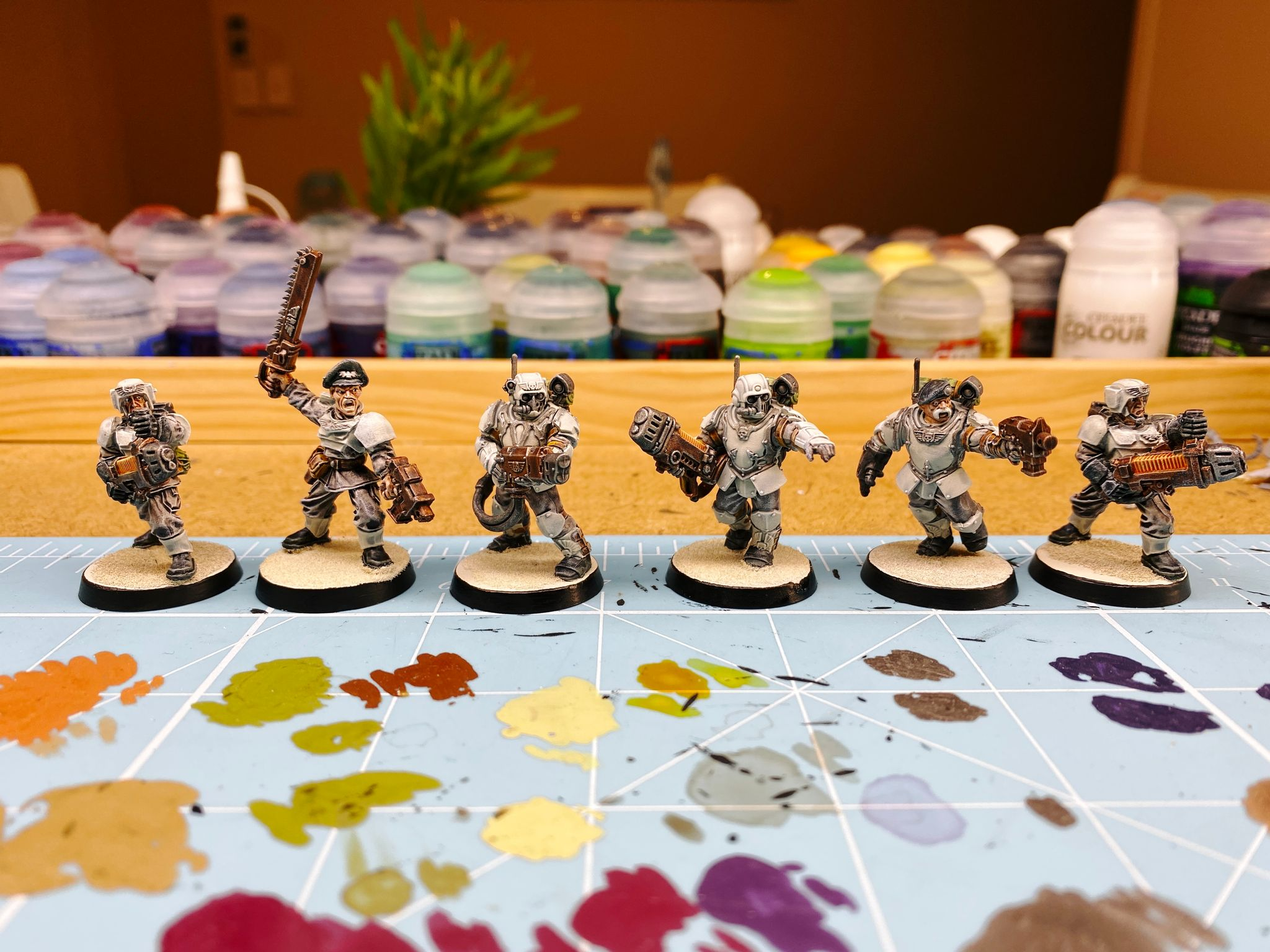 A photo of six Astra Militarum guardsmen from Warhammer 40,000. Their armour is very light grey bordering on white like they're ready for winter action. They're brandishing a variety of weapons, one is a sergeant holding a chainsword above his head, another has a sweet handlebar moustache.