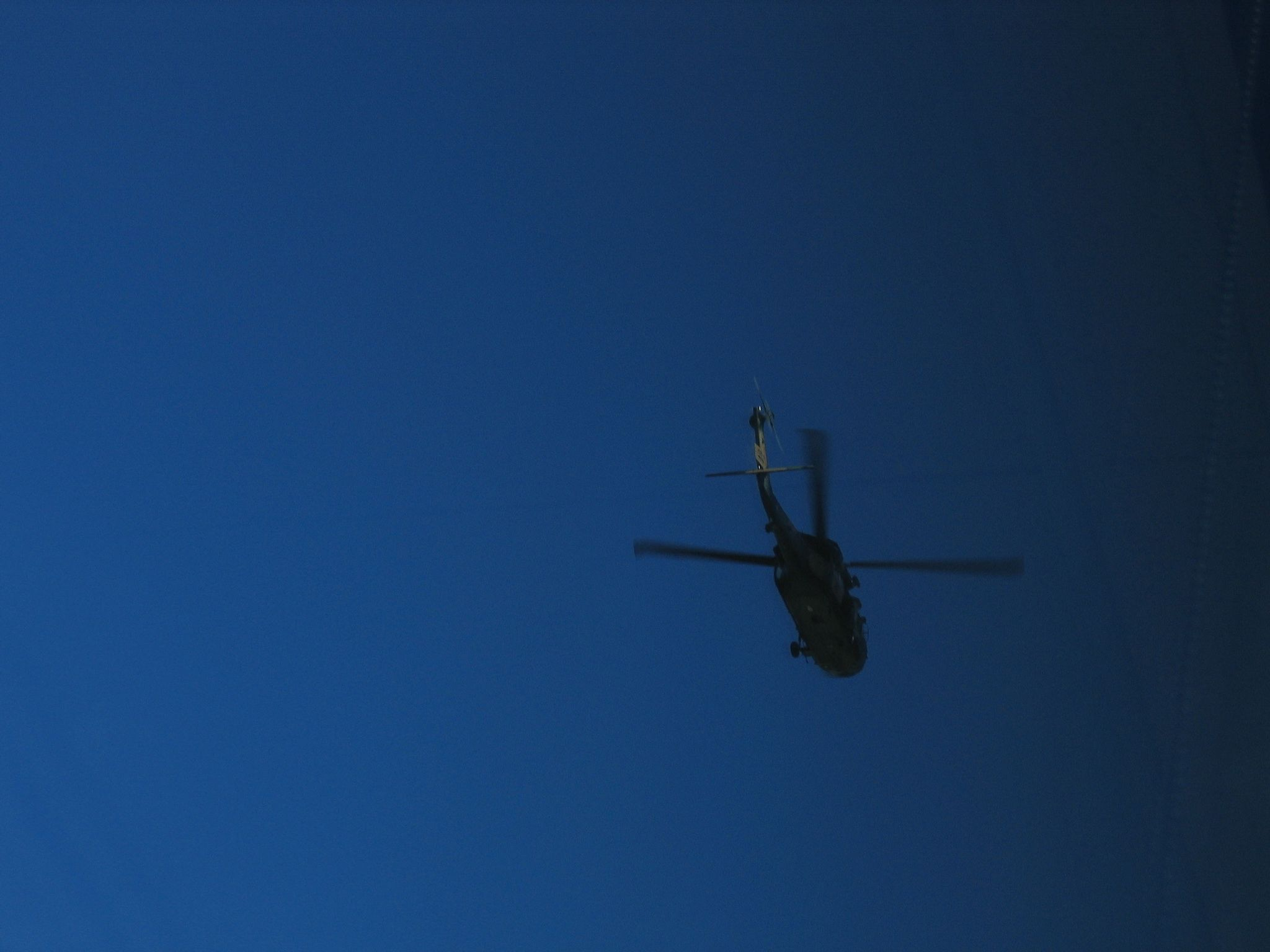 An photo of a Blackhawk Helicoper in the sky.