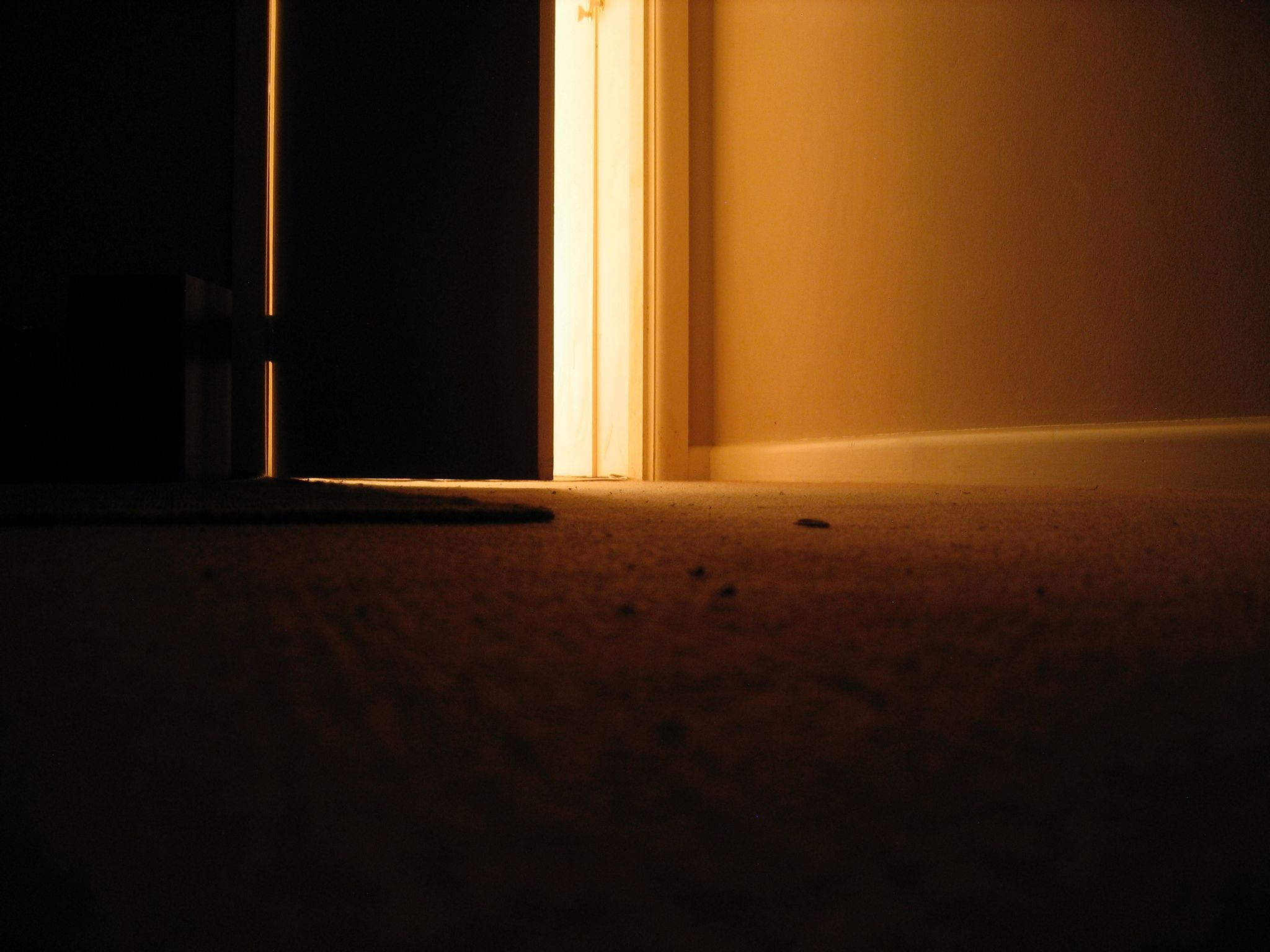 A long exposure photo looking out towards a partially-closed door, taken with the camera sitting on the floor. The room is dark and there's very warm light coming in from the doorway, and there's something indistinct lying on the floor next to the door. A t-shirt, perhaps?