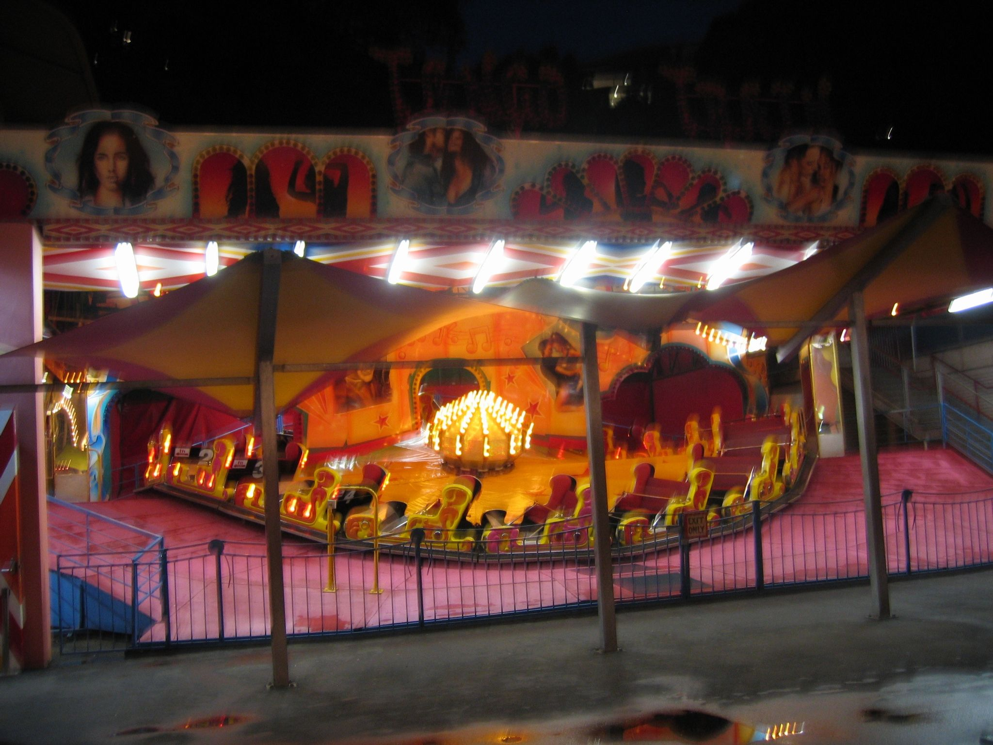 A blurry photo of a fairground ride with seats that move around a track in a loop.