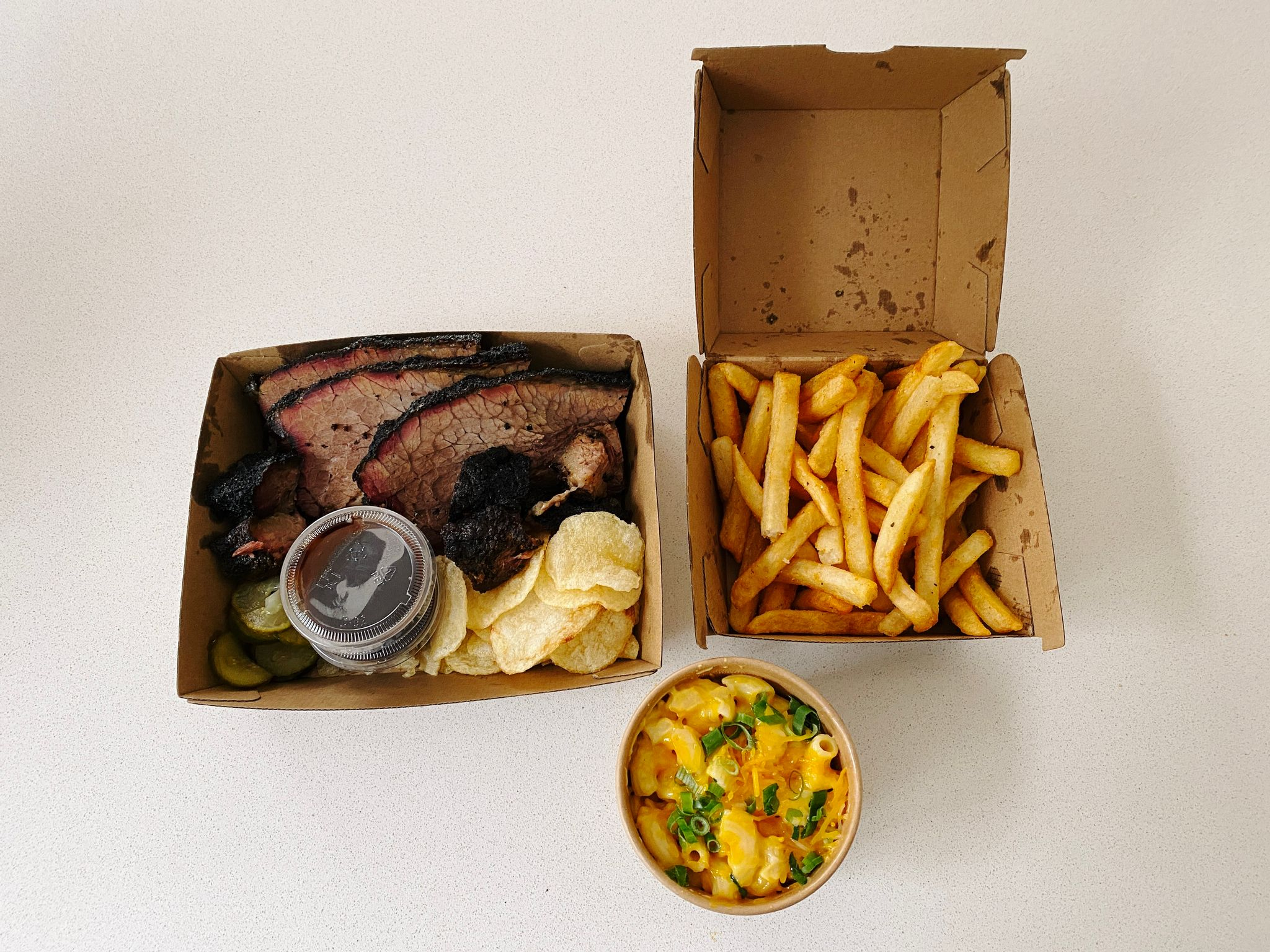 A photo of a box of hot chips, a container of mac and cheese, and beef brisket with chips and pickles.