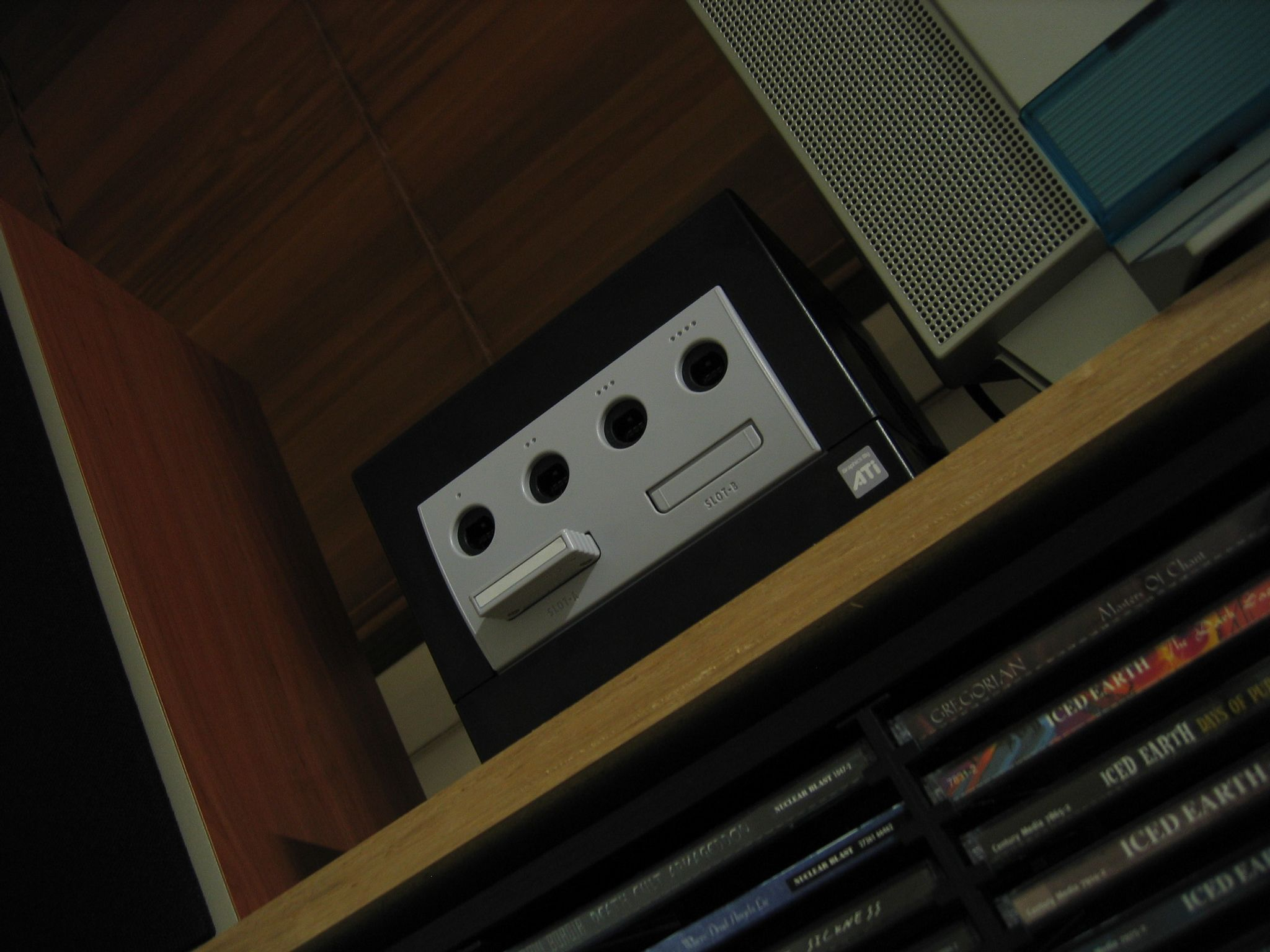 A photo of a Nintendo GameCube on a shelf, taken from below the shelf and looking up at an angle.
