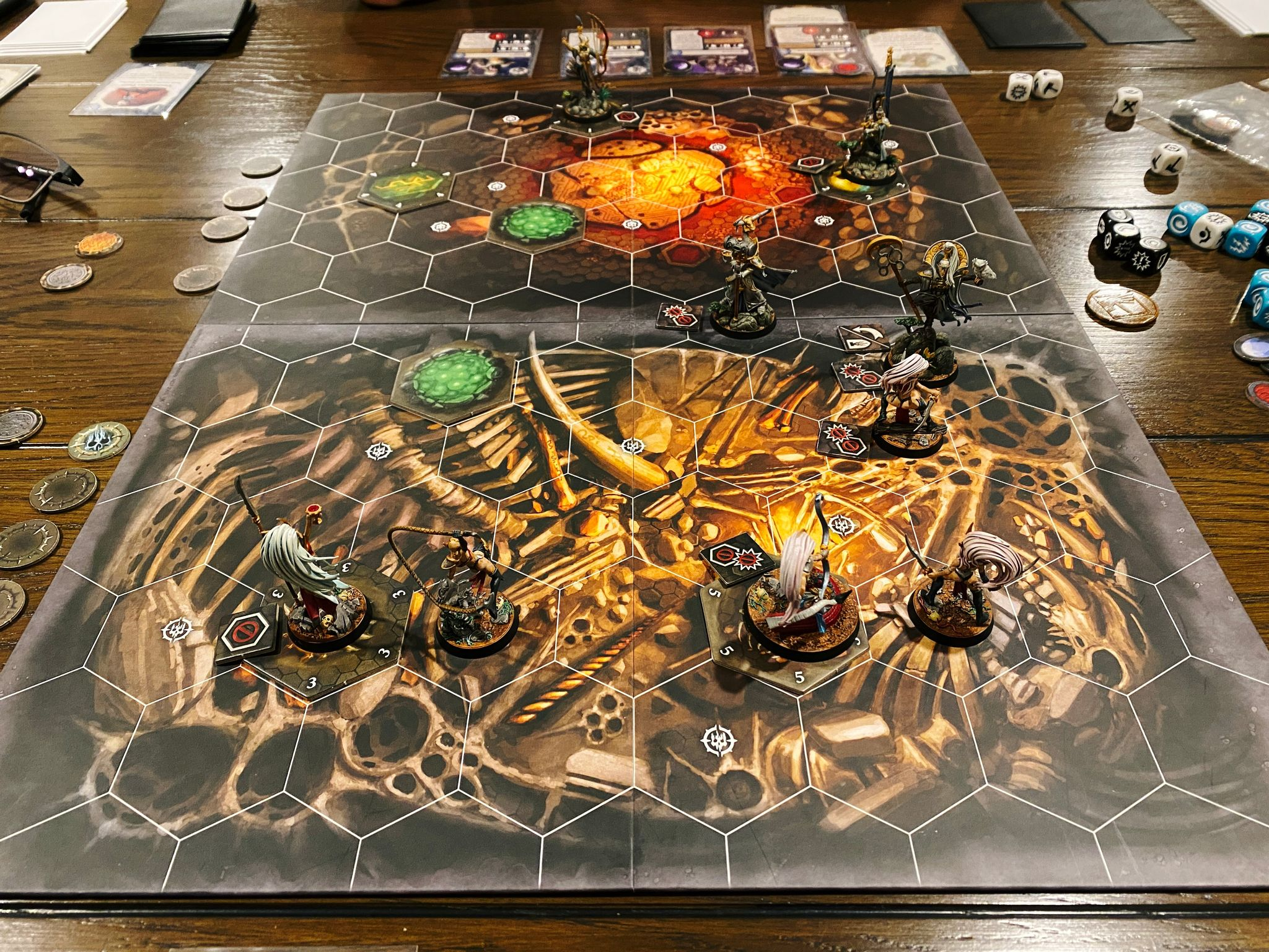 A photo of a Warhammer Underworlds game board, consisting of hexagonal tiles. There's a number of miniatures on it, on the far side are the Lumineth Realm-lords, all high and mighty-looking aelves, and on the other is Morgwaeth's Blade-coven who are also aelves but wearing significantly less armour and looking much more feral. One of the Coven is a snake from her waist down.