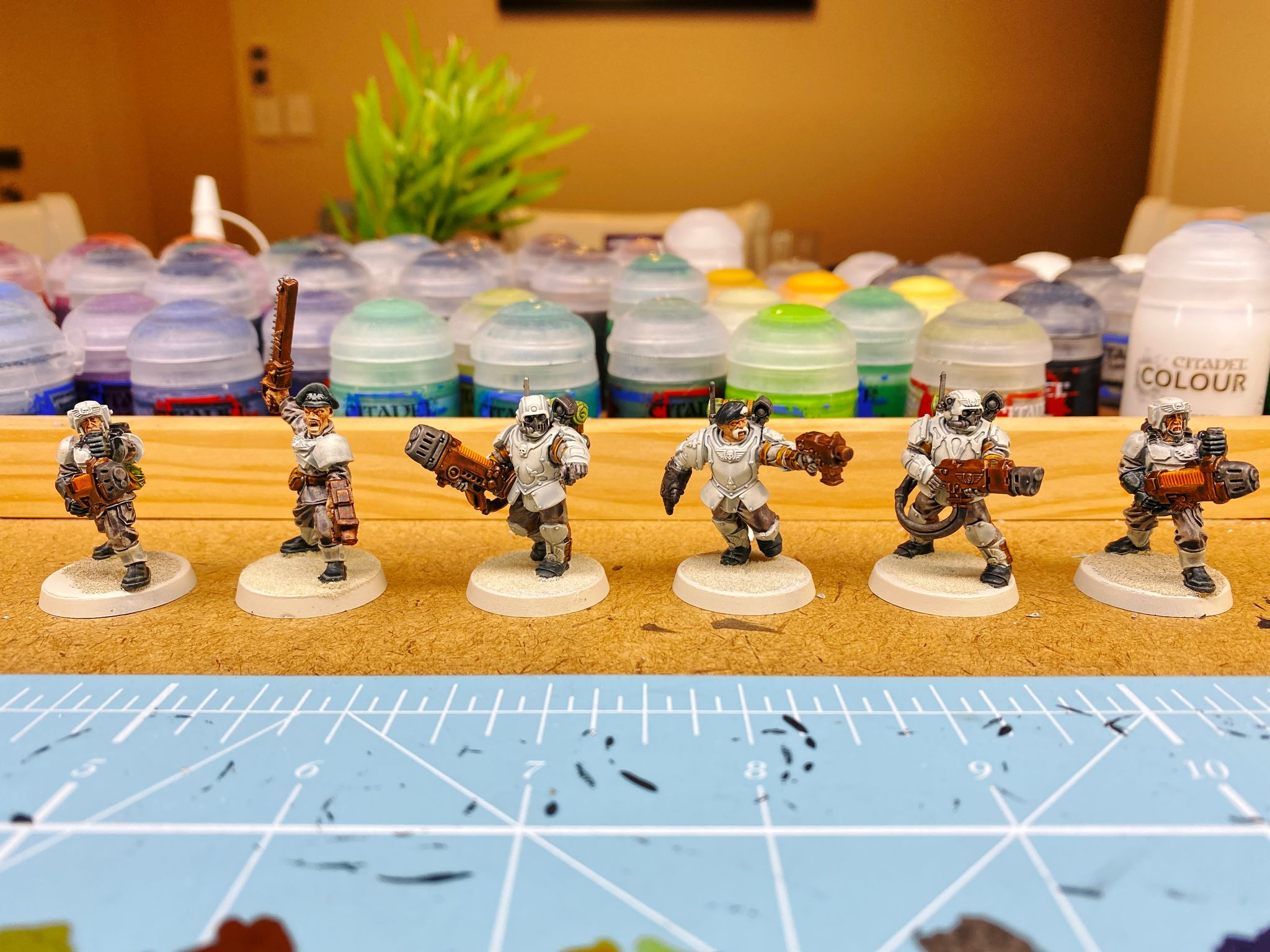 A photo of six mostly-painted guardsmen from Warhammer 40,000. Their armour is very light blue/grey, three of them are wearing heavy armour and one has a helmet, another is a sergeant with a beret and brandishing a chainsword, two more are holding very large plasma guns, as is one of the heavily-armoured ones. One of the heavily-armoured ones has a beret and a sweet handlebar moustache.
