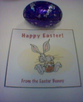 "A photo of an easter egg sitting next to a piece of paper that says ""Happy Easter! From the Easter Bunny"" on it, with a cartoon Easter Bunny in the middle."