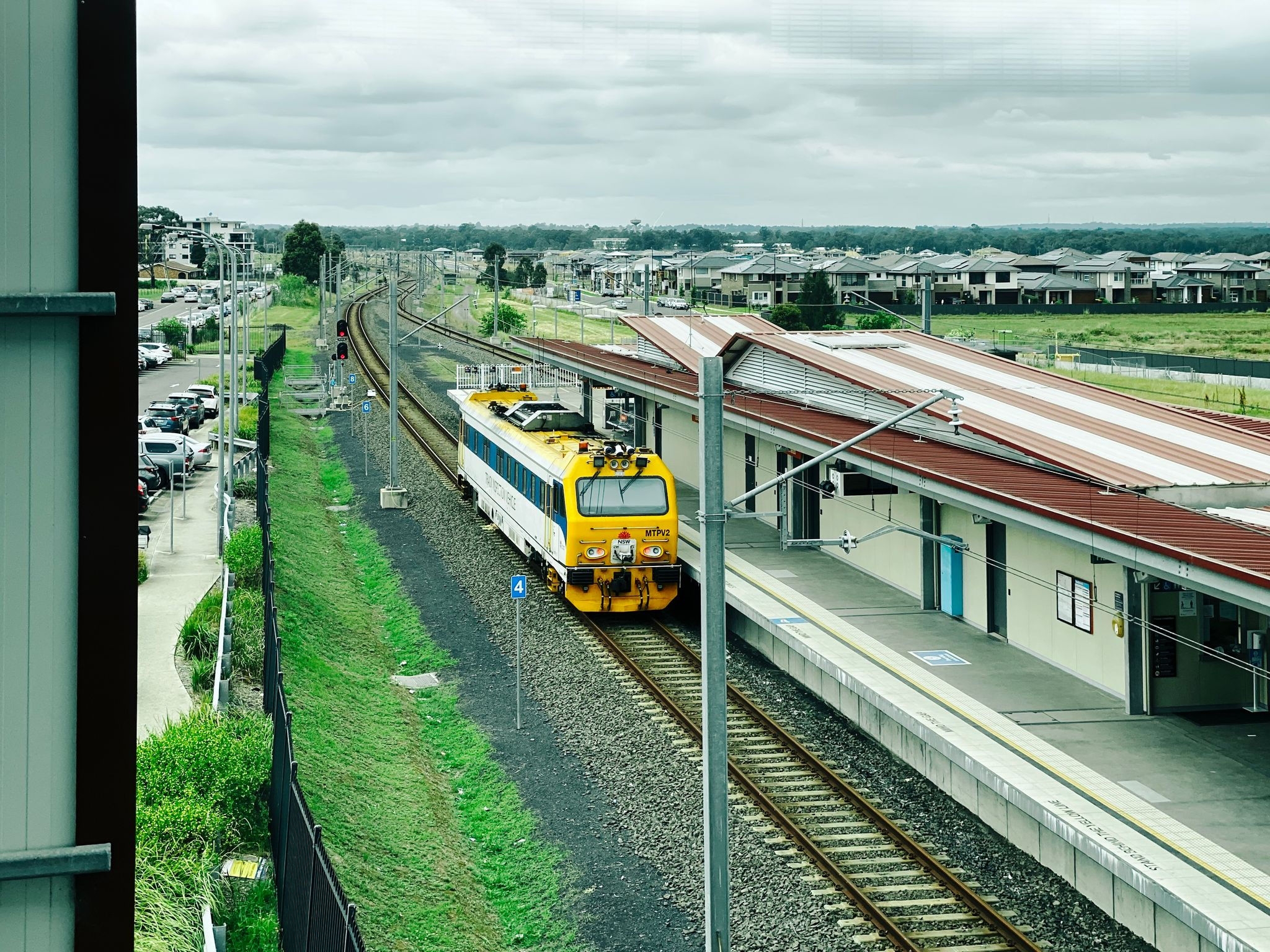 A photo of a train track inspection vehicle sitting alongside a train platform.
