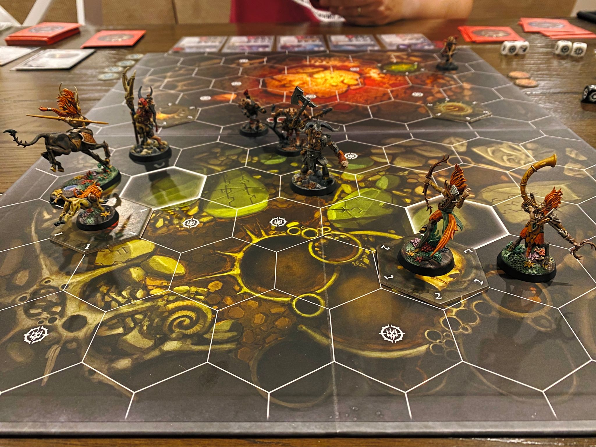 A photo of the game board of Warhammer Underworlds: Beastgrave. It has a bunch of hexagonal tiles on it, and the two opposing forces are elves that have red hair and backwards-facing goat legs, and a bunch of rampaging beastmen.