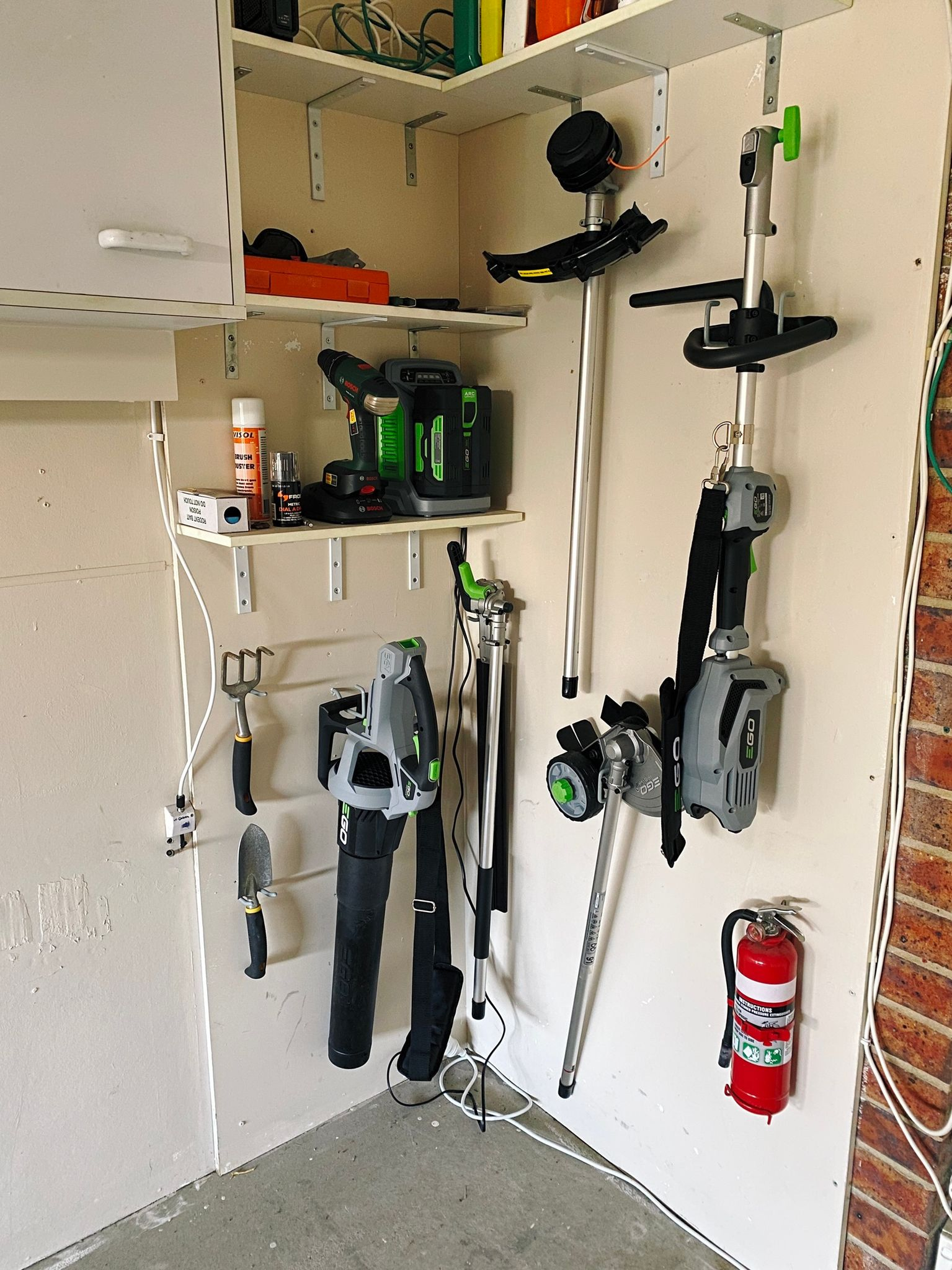 """A photo of a corner of our garage with all of our new garden equipment mounted on the wall with hooks: the """"Power Head"""" that holds the battery for the edger, hedge trimmer, and line trimmer attachments, as well as the leaf blower. There's also a small fire extinguisher, and small garden fork and spade."""