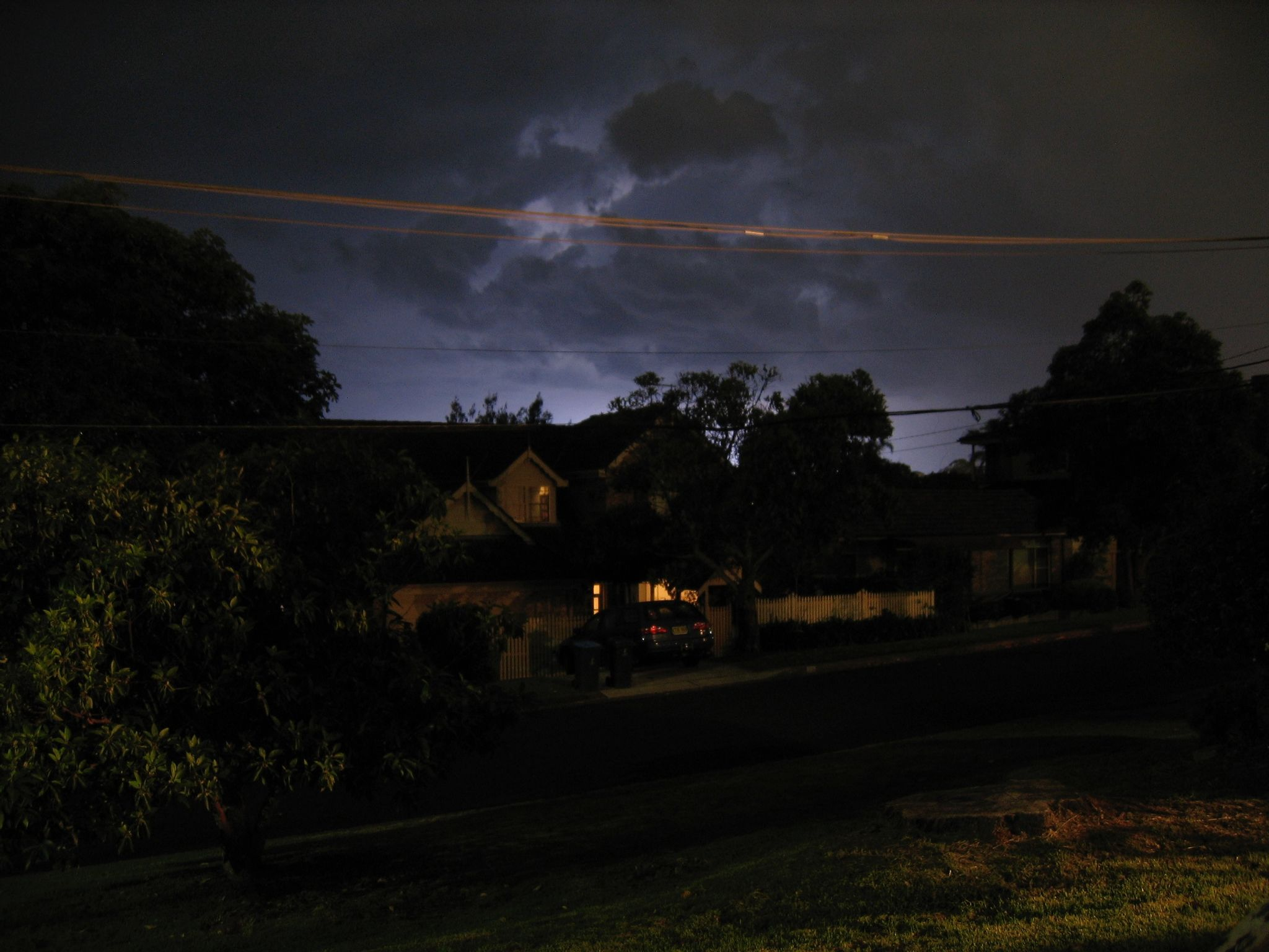 A long-exposure nighttime photo looking up over houses and trees at clouds that are being lit up from lightning strikes.