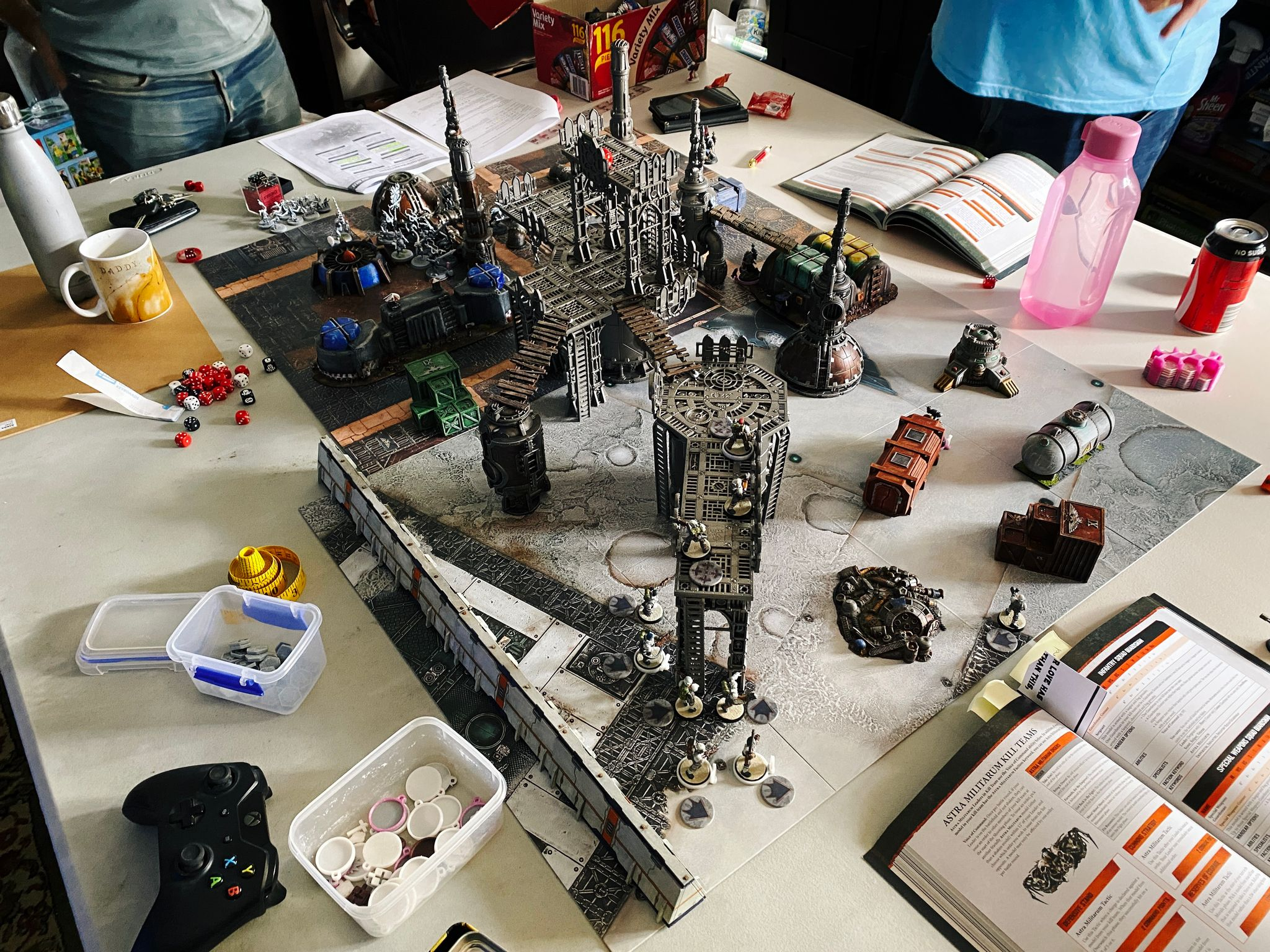 A photo of a 3-player game of Warhammer 40,000: Kill Team. The terrain is all industrial, with lots of pipes and metal structures, as well as shipping containers and cargo crates, and some bridges connecting the various upper levels.