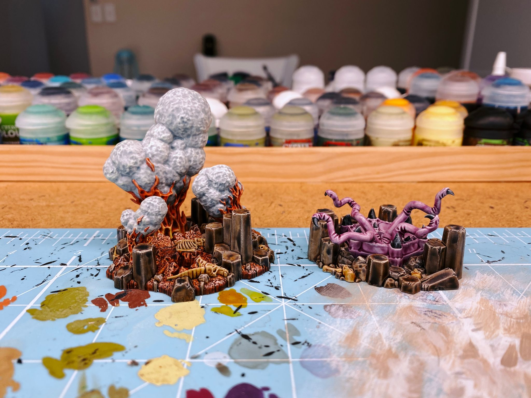 "A photo of two pieces of terrain from the Warhammer Underworlds ""Primal Lair"" box. One is rocky and has fire and smoke billowing up from holes in the ground, and the other is a pinky/purple freaky-looking four-tentacled thing nestled in a series of basalt columns."