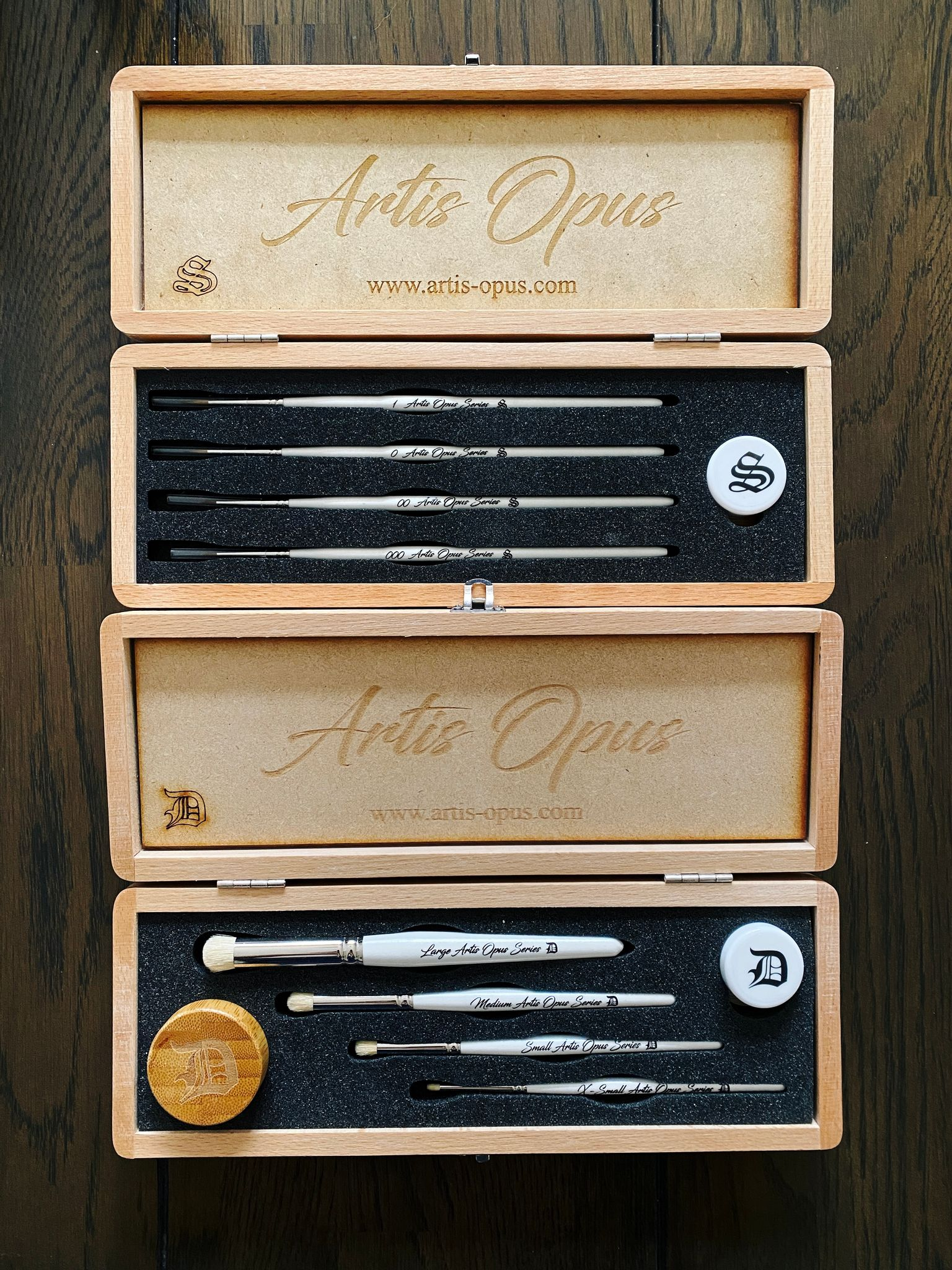A photo of two wooden boxes with fancy Artis Opus brushes in them. One is a set of four regular brushes, the other is set of four drybrushes.