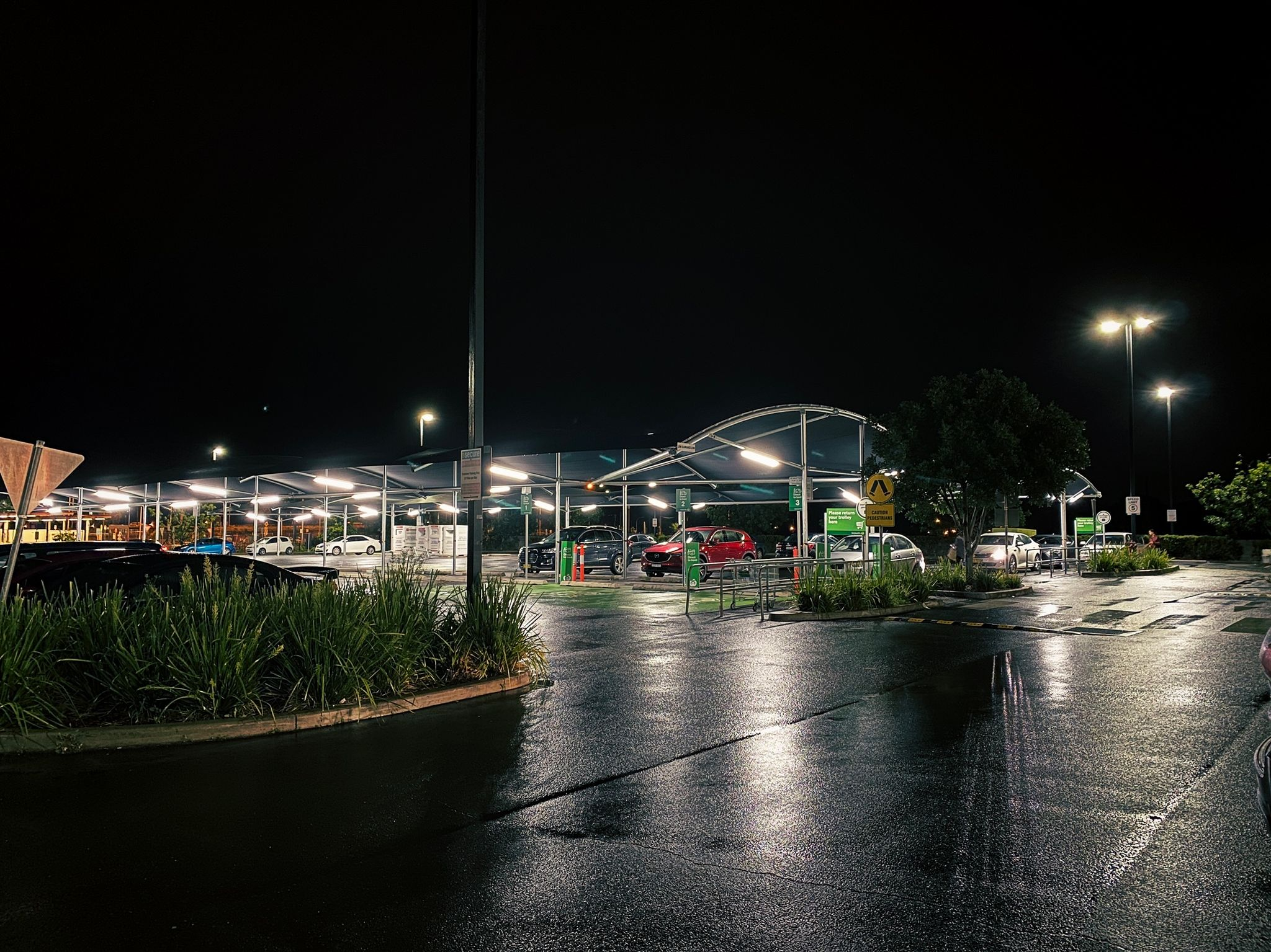 A photo of an open-air car park at night, with shade sails and a few cars. It's been raining and the ground is reflecting all the lights.