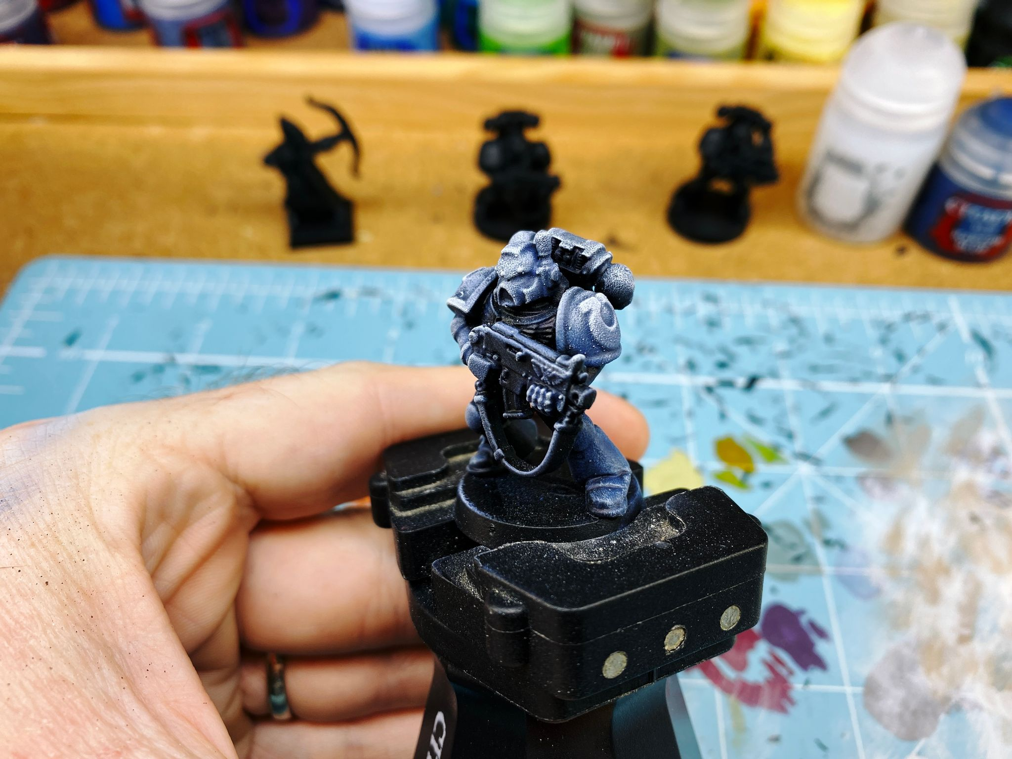 A photo of one of the old early 2000s Warhammer 40,000 Space Marine miniatures that's base-coated black but drybrushed in a gradient in blue-greys up to almost white in a lovely gradient.
