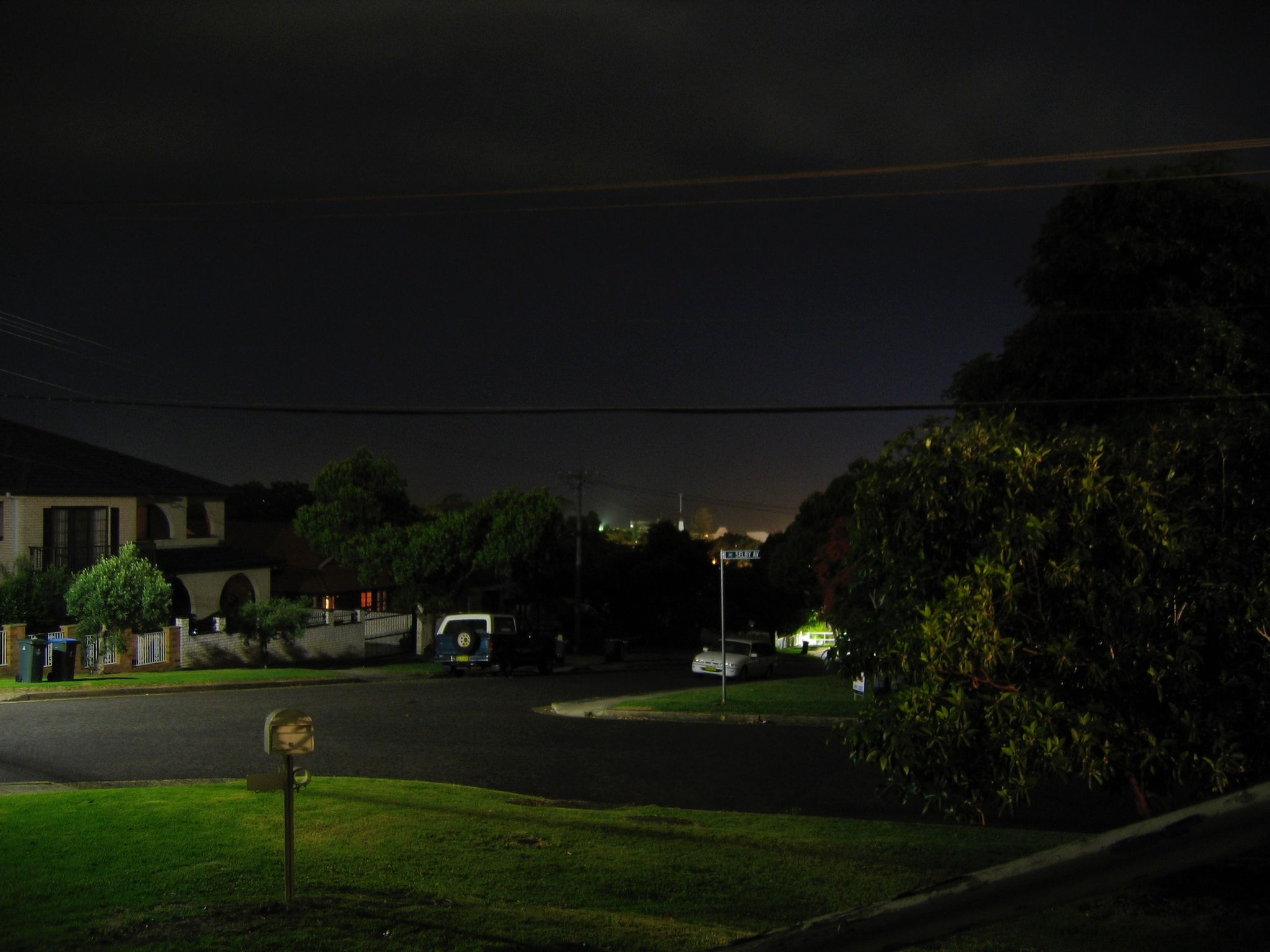 A long-exposure nighttime photo looking out at the street in front of a house. The left side is lit by a street light, and in the distance over the trees there's lights visible from distant buildings.
