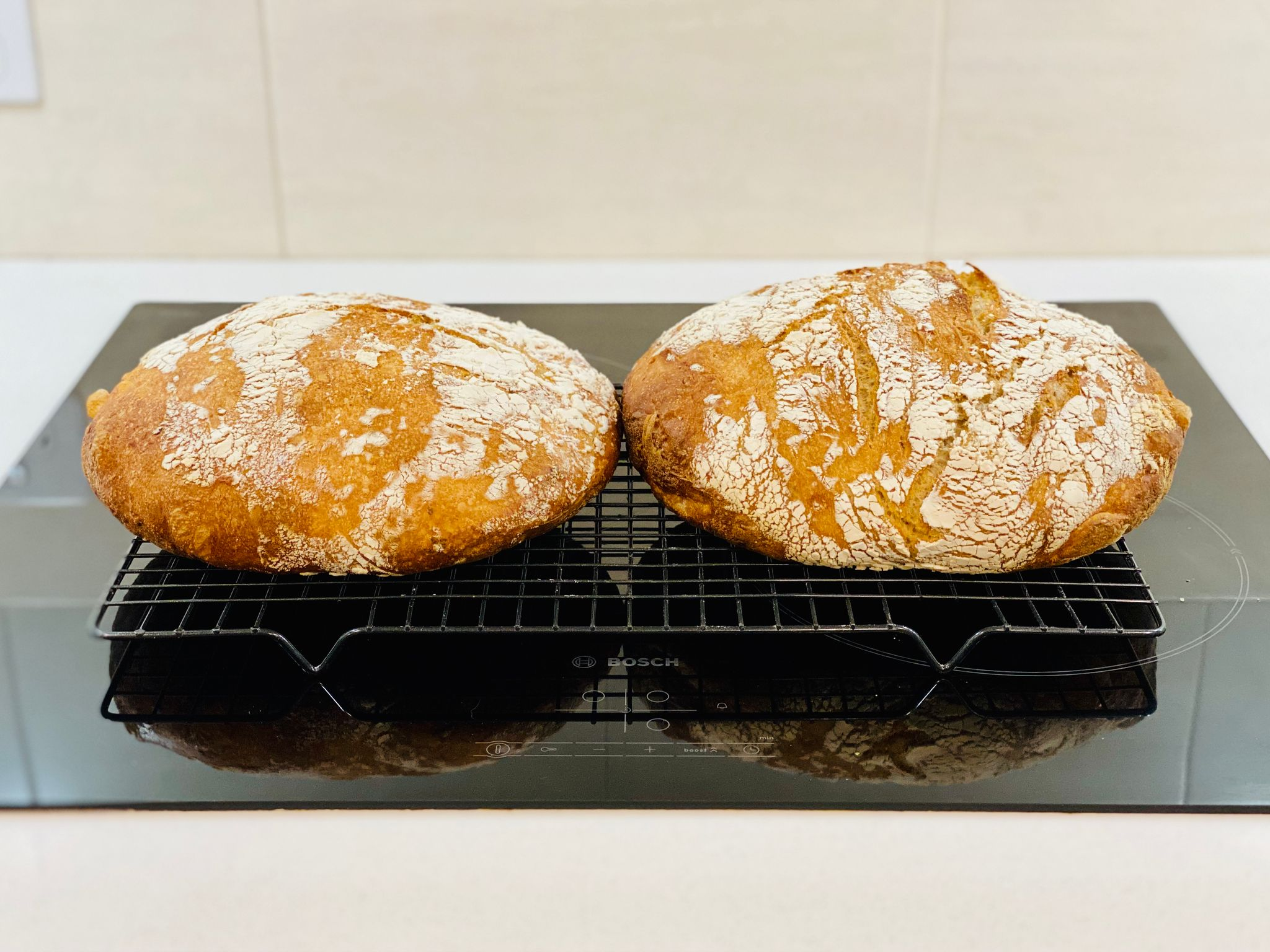 Two round but also flat loaves of bread sitting on a cooling rack.