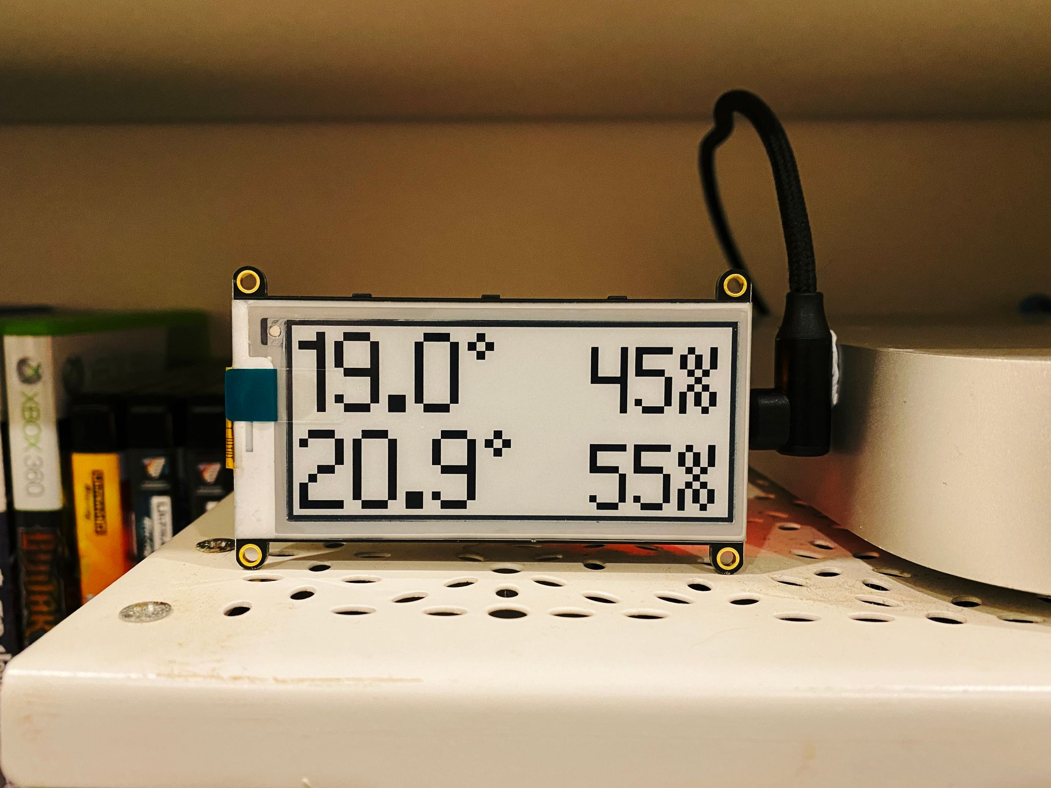A photo of an e-ink display with a blocky pixel font, showing the current outdoor and indoor temperature and humidity.