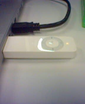 A photo of an original iPod shuffle plugged into the side of a laptop.