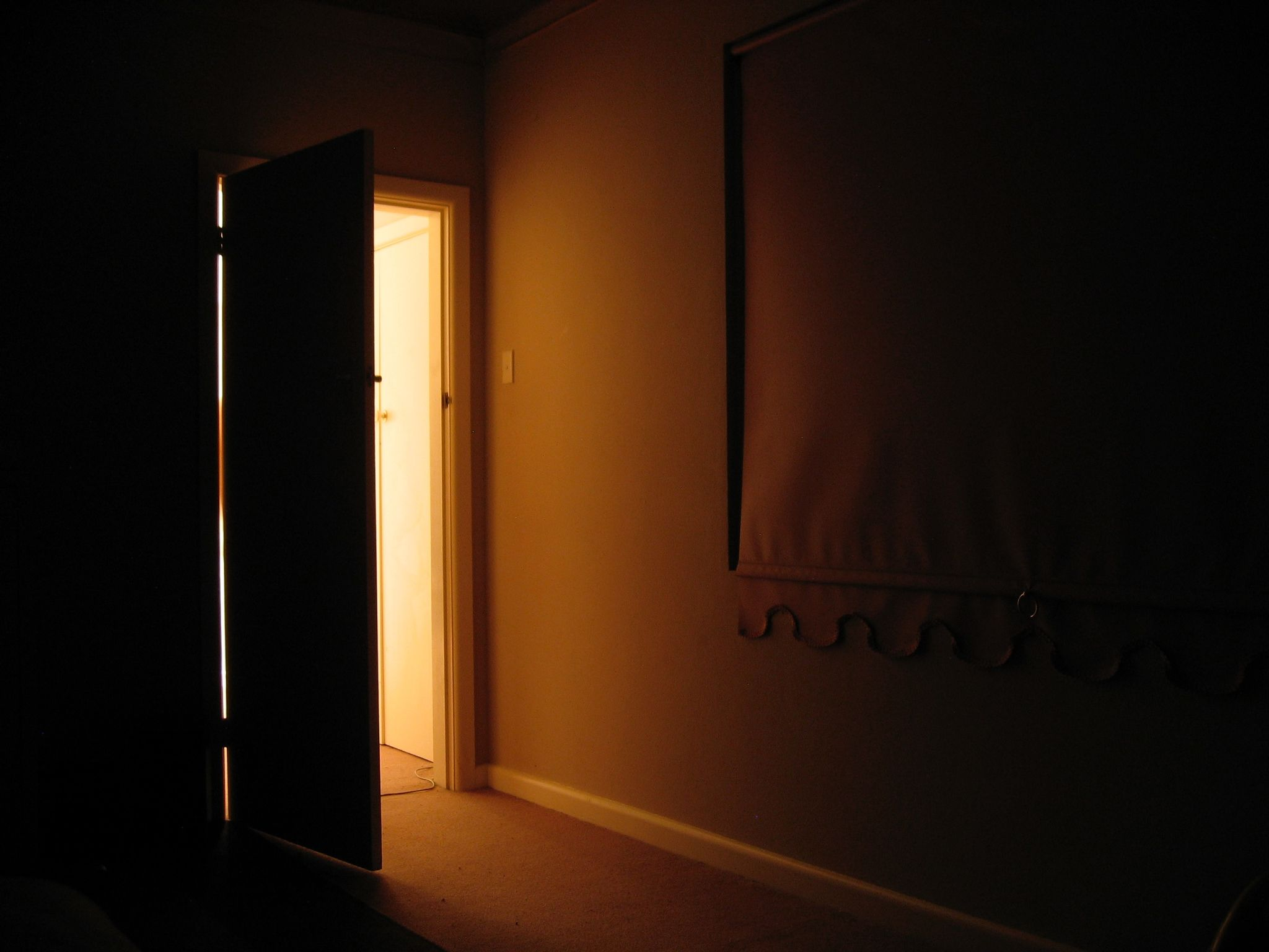 A long exposure photo looking out towards a partially-visible door. The room is dark and there's very warm light coming in from the door.