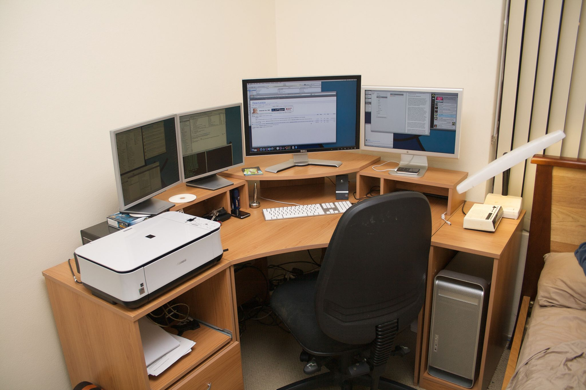 """A photo of a corner desk with a 24"""" Dell Monitor in the middle,  a 20"""" Apple Cinema Display to the right, and two 17"""" 4:3 Samsung monitors to the left."""