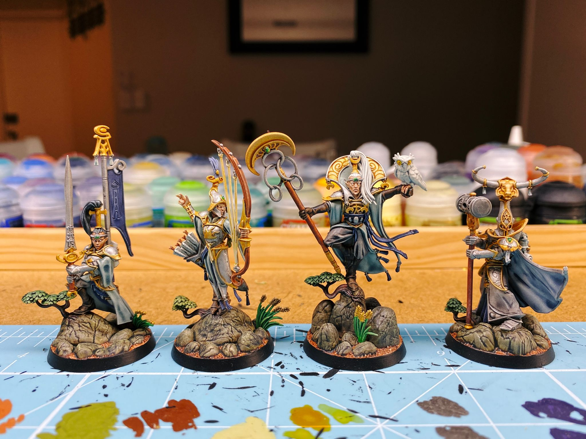 A photo of four fully-painted miniatures, the elves from the Warhammer Underworlds: Direchasm core set. They have elegant silver armour with gold trim and pale green/blue robes. One has a sword, another has a hammer, a third has a bow, and the leader has a staff in one hand and a white owl with yellow eyes sitting on his other hand.