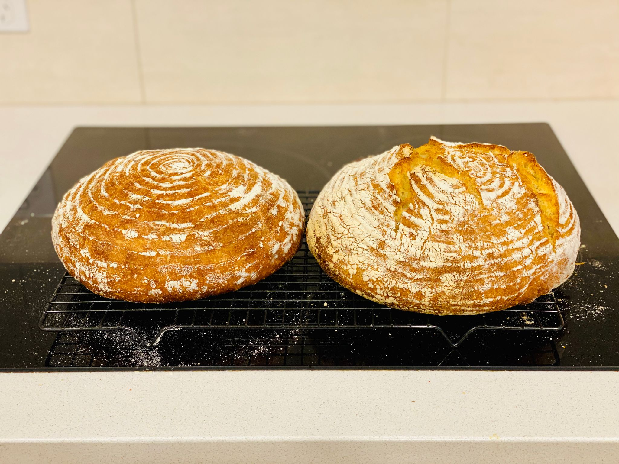 Two round golden loaves of bread sitting on a cooling rack.