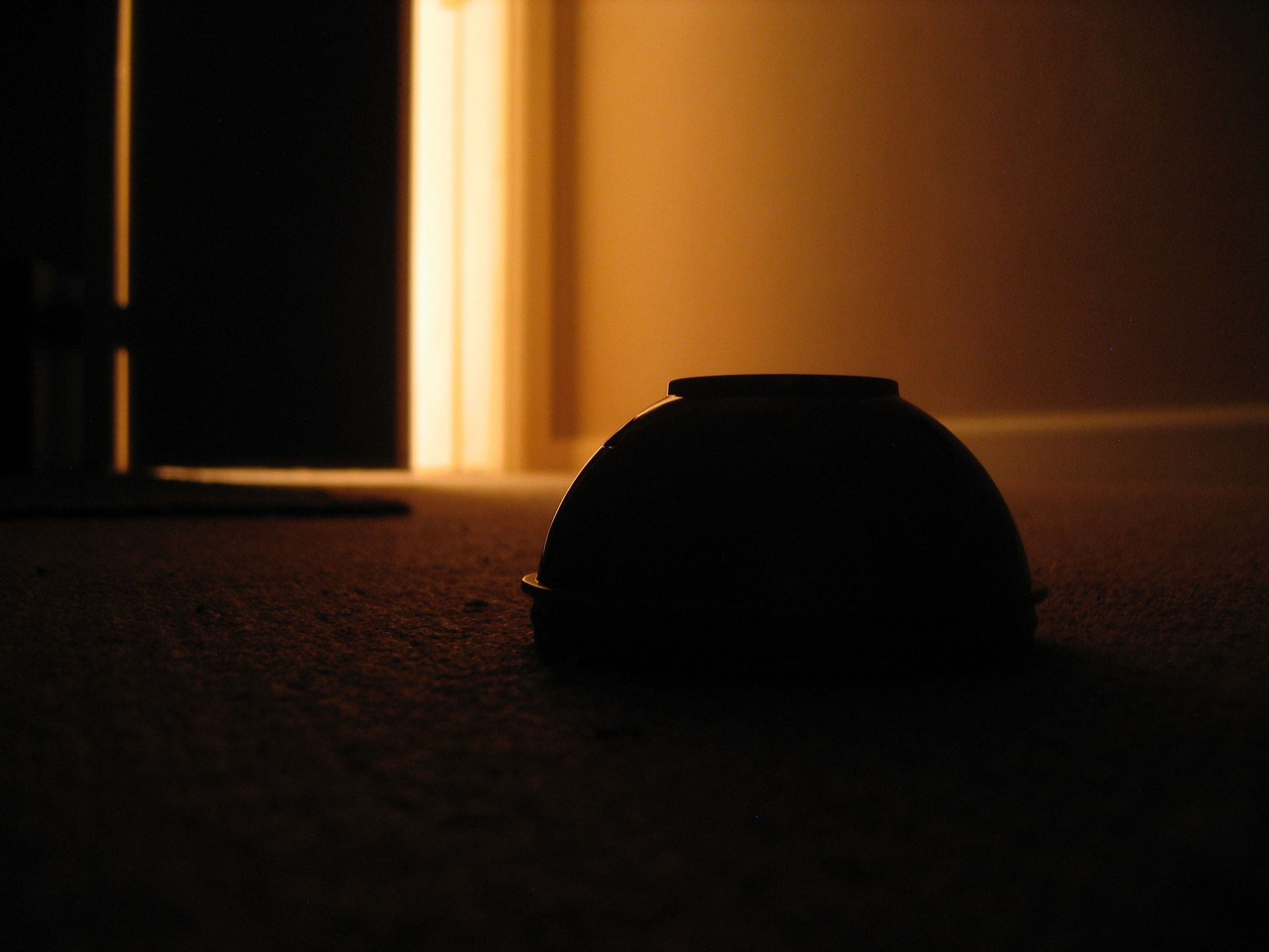A long exposure photo looking out towards a partially-closed door, taken with the camera sitting on the floor. The room is dark and there's very warm light coming in from the doorway. An upside-down plastic toy bowl is sharply in focus in the middle of the frame, and the door is out of focus. The light is reflecting cleanly off the side of the bowl.