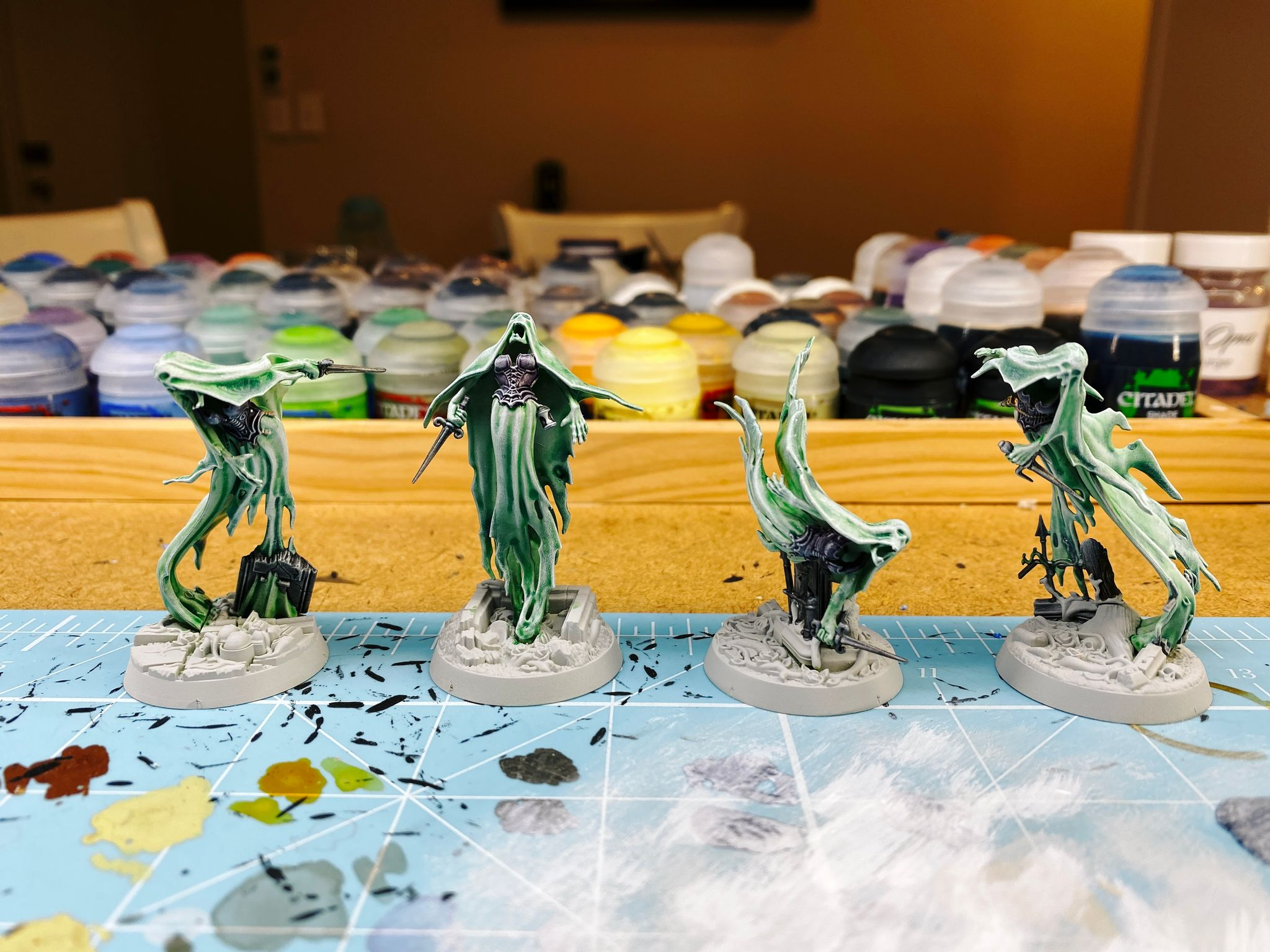 A photo of the four miniatures of Lady Harrow's Mournflight from Warhammer Underworlds. They're spirits and modelled to look like they're very ephemeral and wispy and flowing. They're partially painted, the wispy bits are a sickly green colour with a smooth gradient into white at the edges and raised areas.