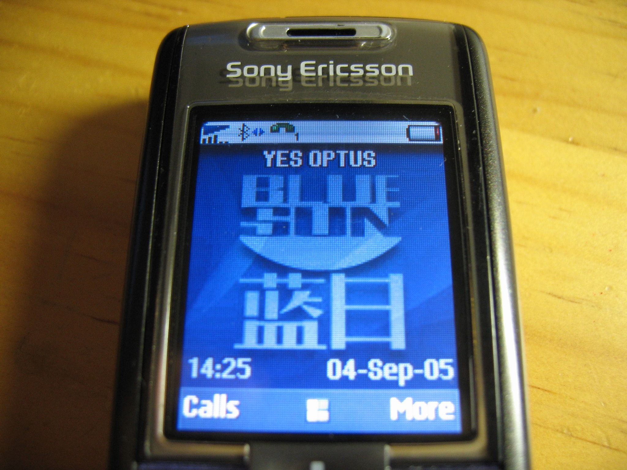 "A photo of the screen of a Sony-Ericsson T630 phone. The background is the Mac OS X blue swirls, with the ""Blue Sun"" logo and Chinese writing from the TV show Firefly on top of it."