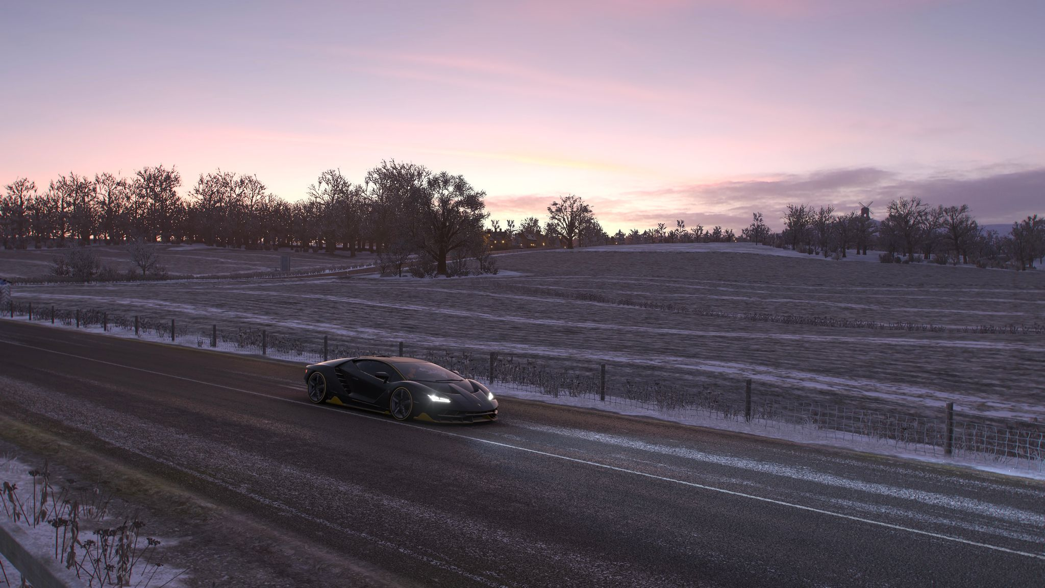 A screenshot from Forza Horizon 4. It's taken just after sunset, with a Lamborghini in the foreground on the road looking back towards where the sun has set. It's winter, and the ground and trees are covered in snow.