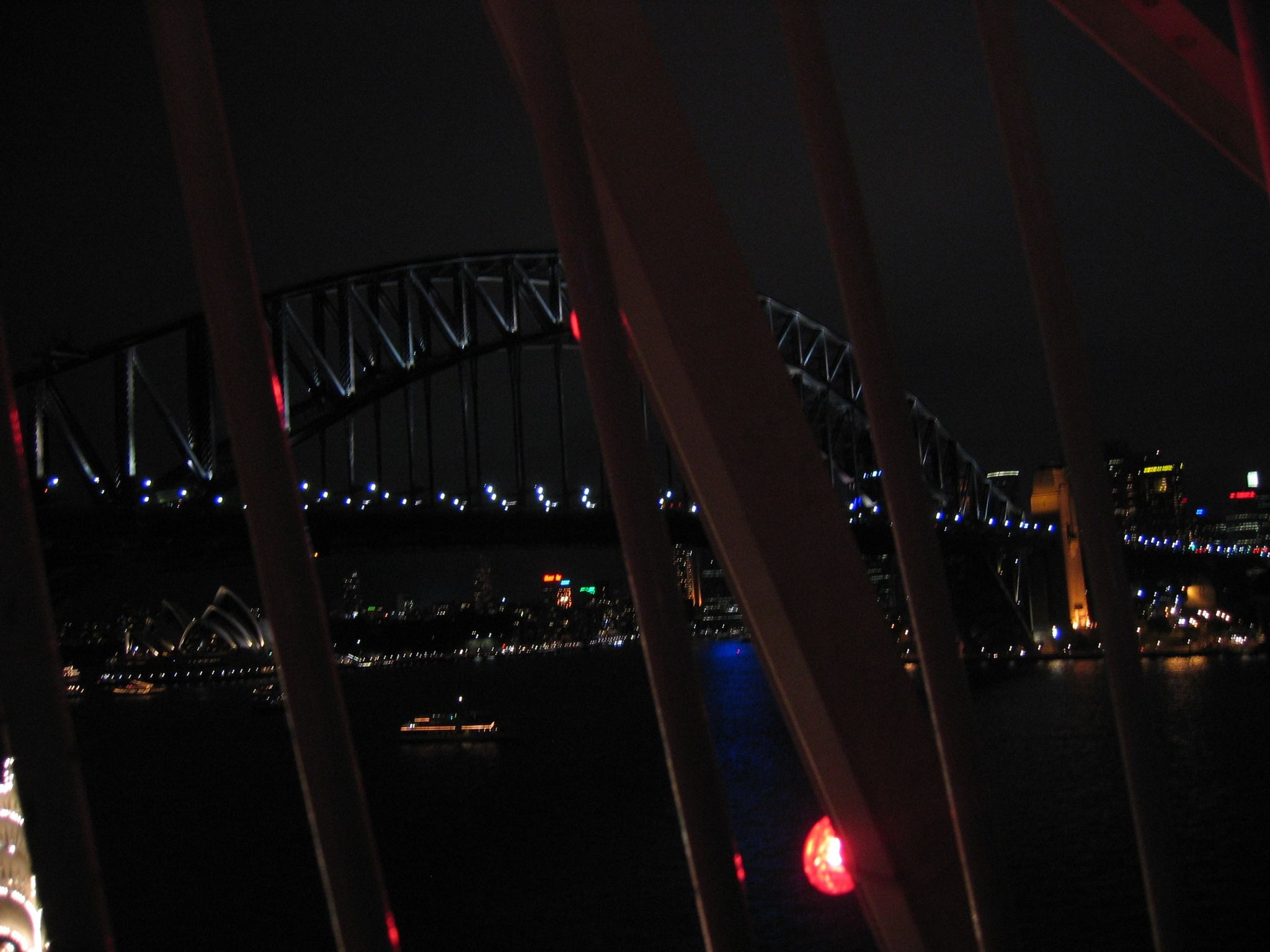 A very dark photo of the Sydney Harbour Bridge, taken from high up on a ferris wheel.