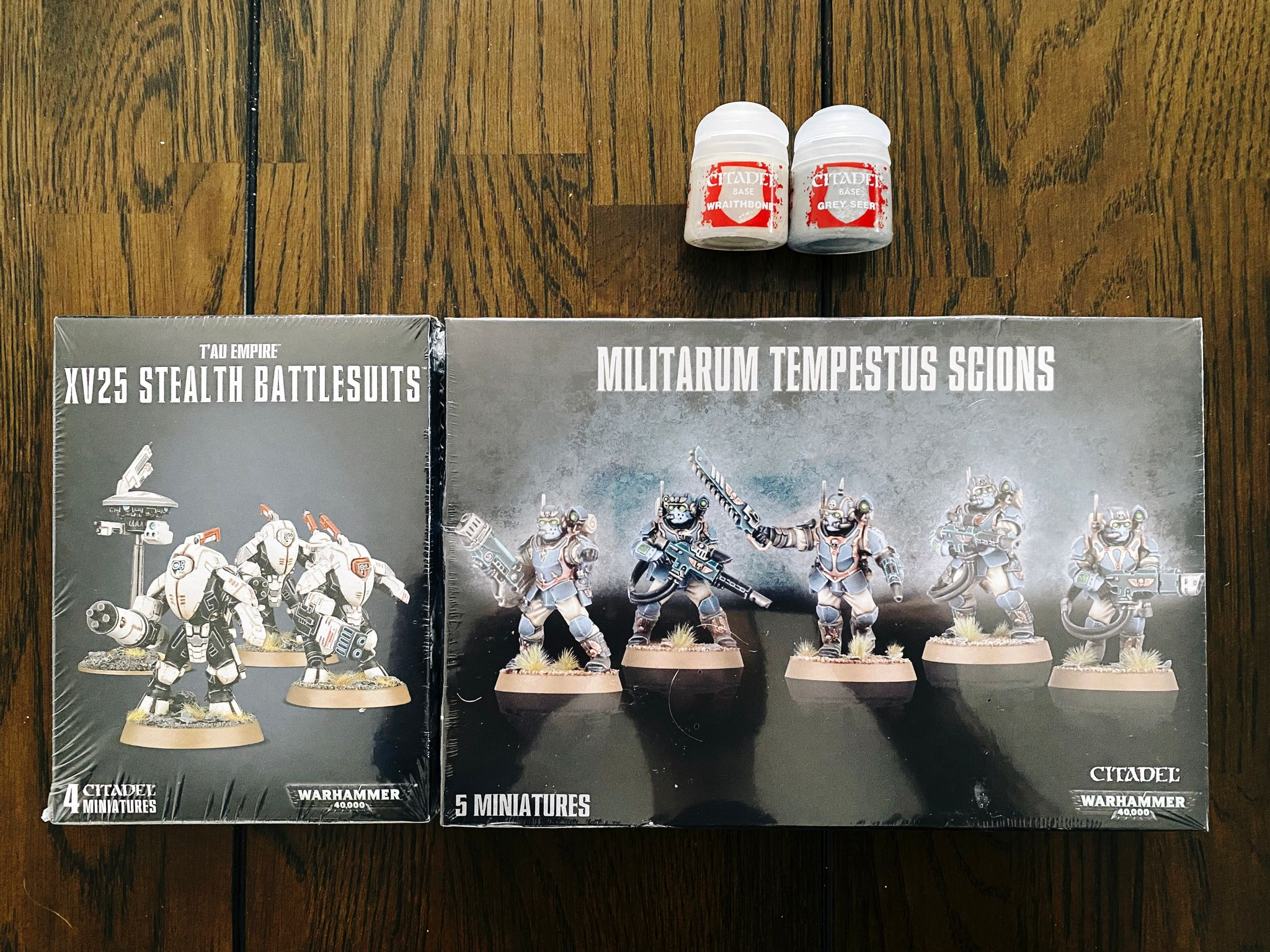 A photo of two pots of miniature paints, a box of three Tau XV25 Stealth Battlesuits, and a box of five Militarum Tempestus Scions.