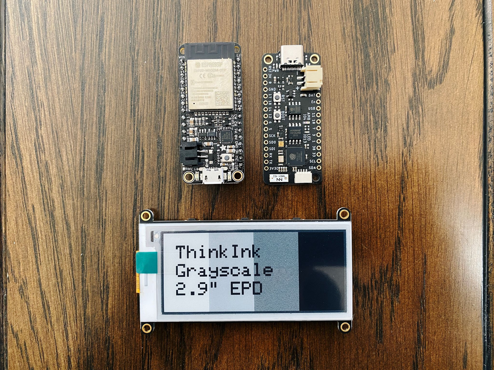 """A photo of two small microcontrollers and a 2.9"""" e-ink display."""