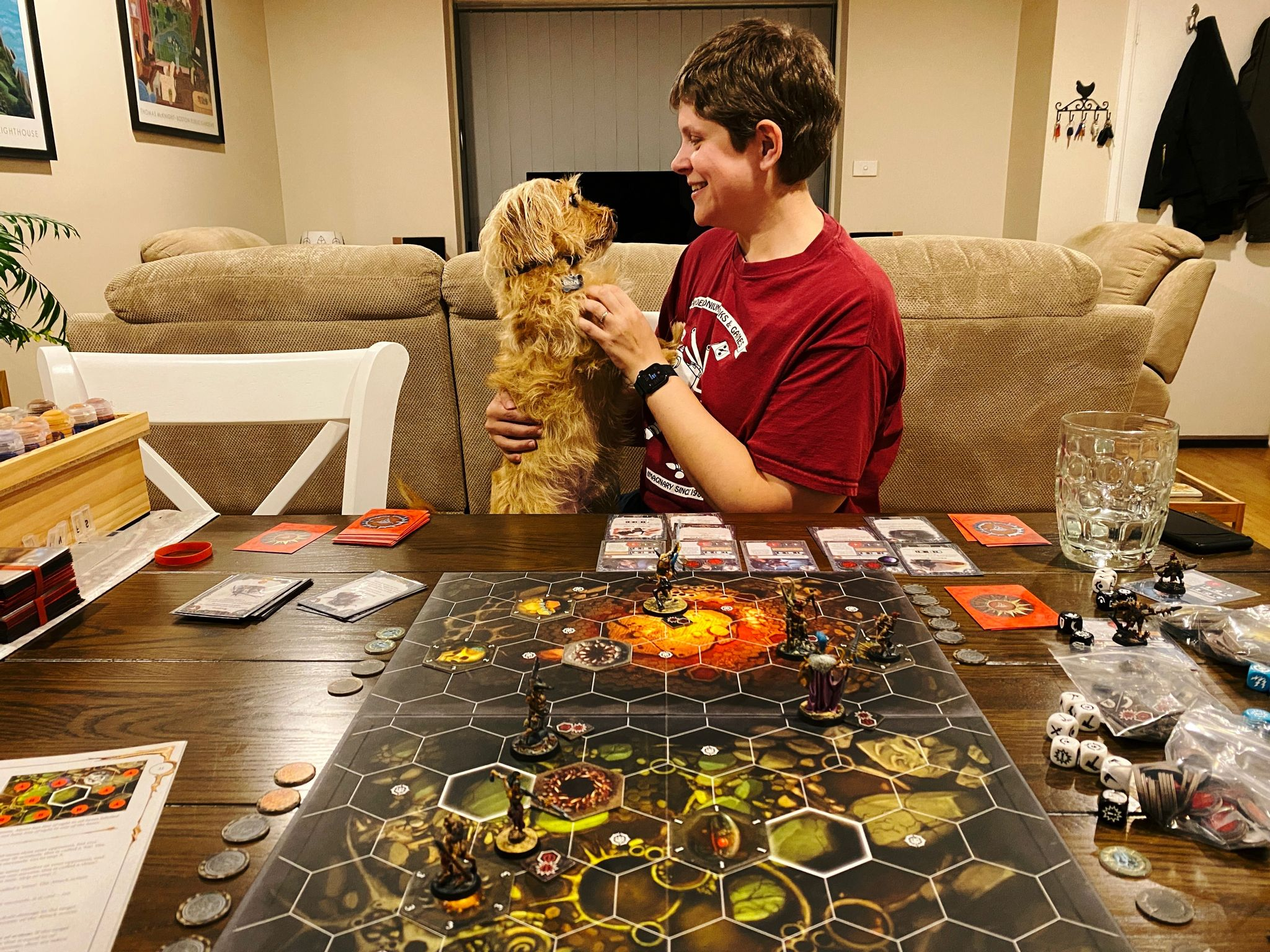 A photo taken across a dining table that has a game board with miniatures on it, and various dice and cards and counters scattered around it. On the other side a white woman with short brown hair is sitting with a small scruffy blonde dog in her lap who's sitting upright and propping himself up on her chest while she scritches him.