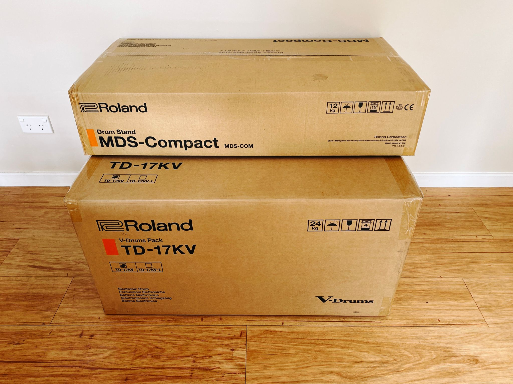 """A photo of two large cardboard boxes, one labelled """"Roland TD-17KV V-Drums Pack"""" and the other """"MDS-Compact Drum Stand""""."""