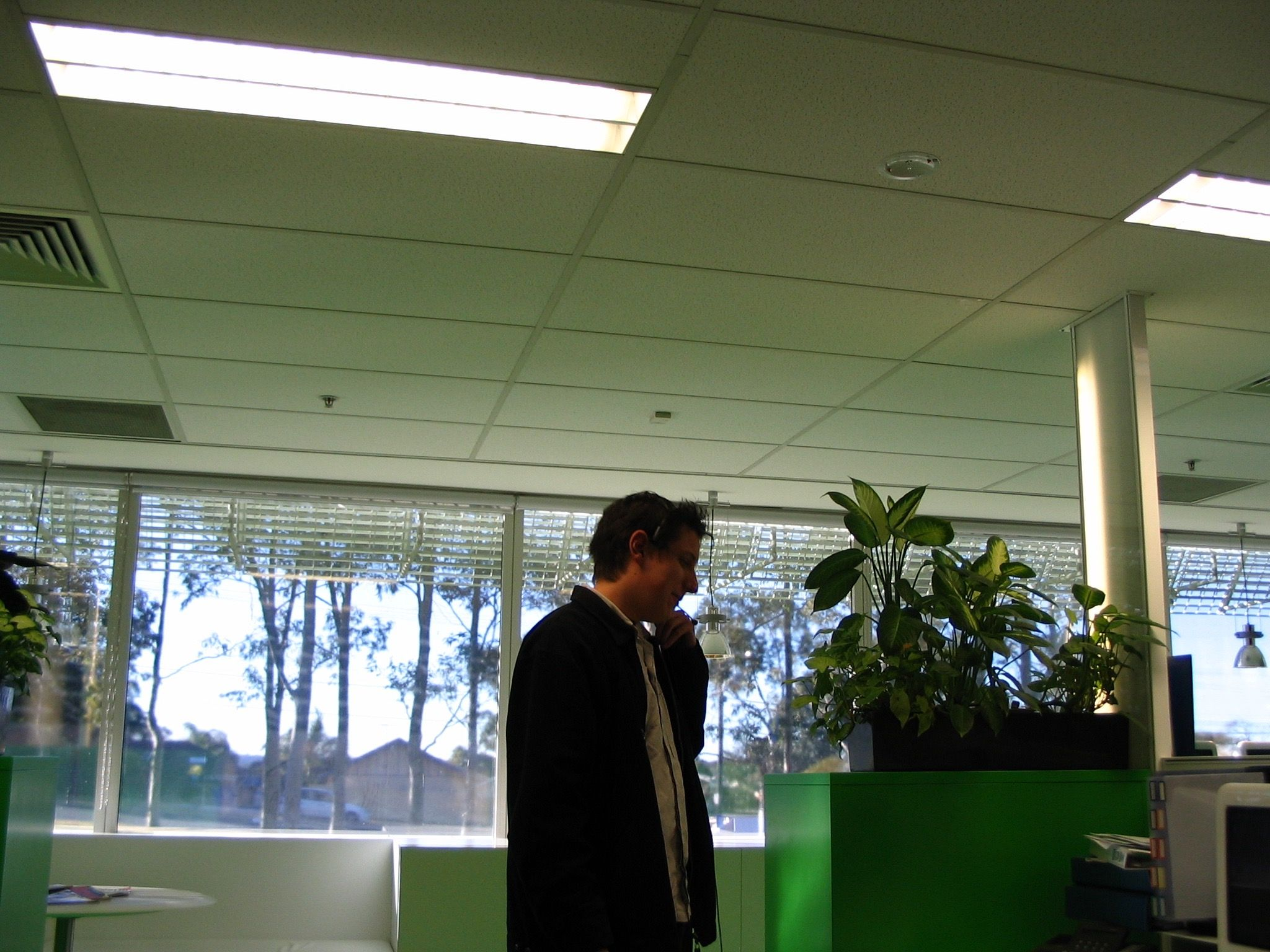 A somewhat backlit side-on photo of a white man in jacket with a call centre headset on, in the middle of talking.