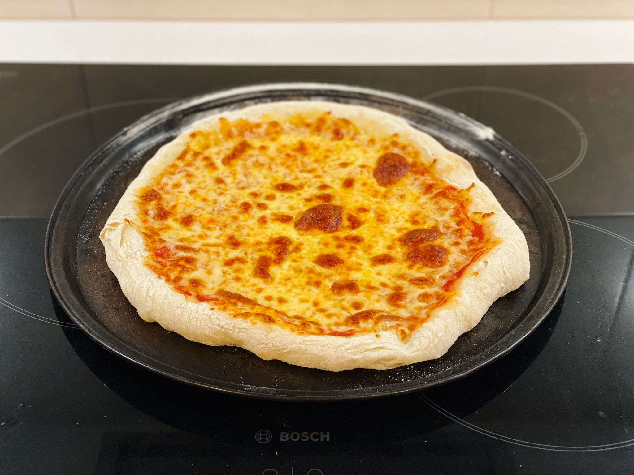 A photo of a homemade pizza with puffy crusts and gloriously cooked cheese sitting on a round pizza tray.