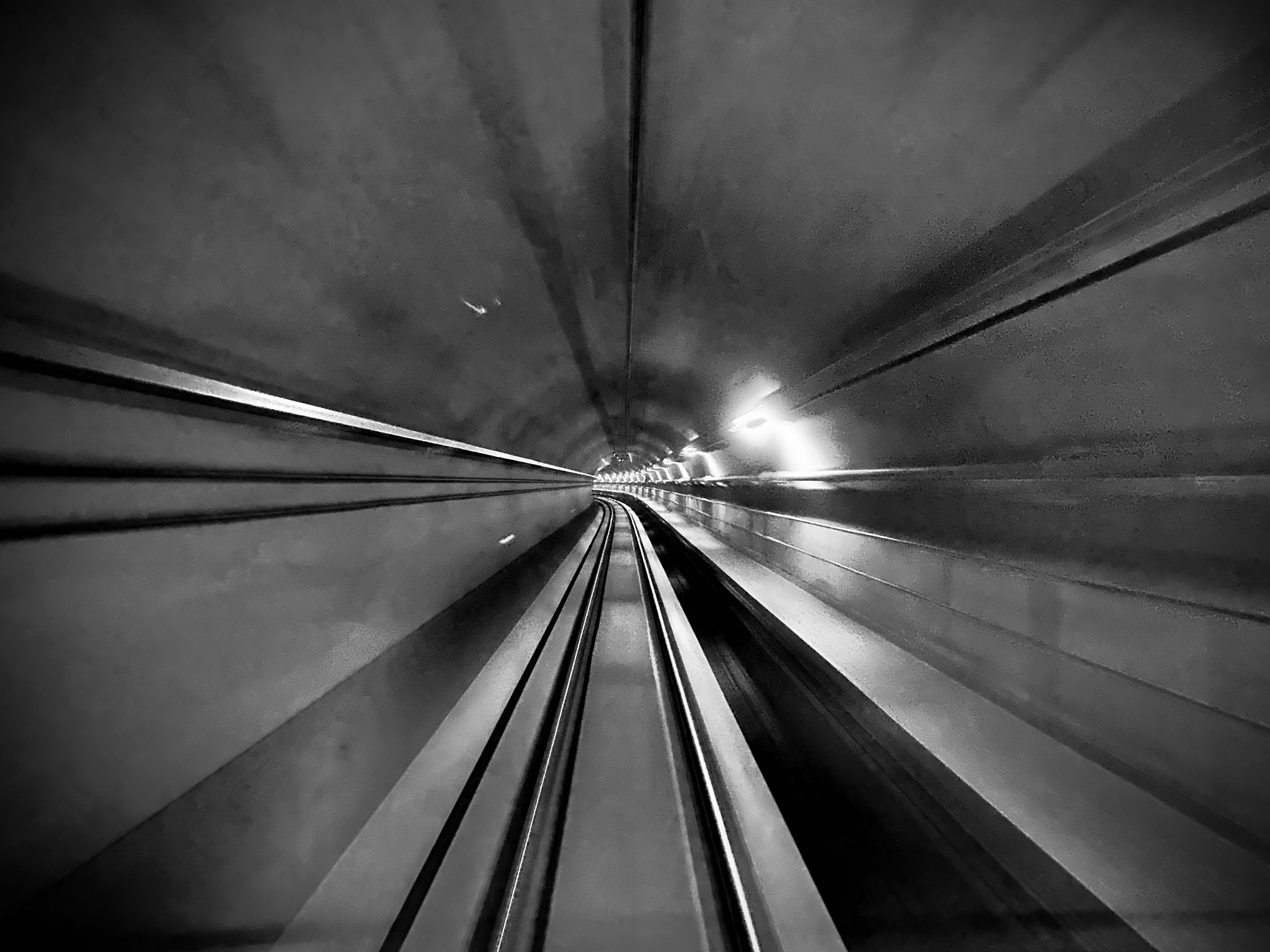 A high-contrast black and white photo out the front of the train from inside one of the tunnels. The tracks are going off around a slight bend and the whole shape of the tunnel is completely round.