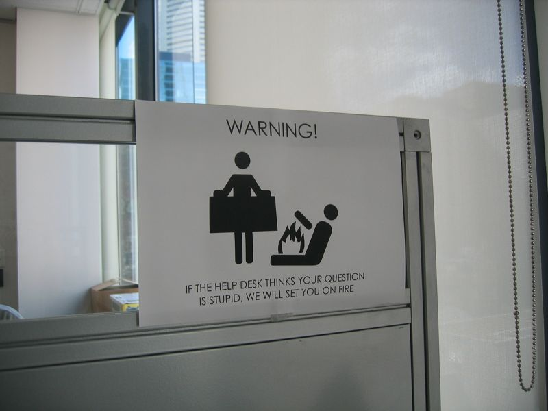 """A photo of a warning sign that's been printed out on paper. The warning sign is the one for a fire blanket with one person on the ground on fire and the other holding the blanket, but underneath it says """"WARNING! If the help desk thinks your question is stupid, we will set you on fire""""."""