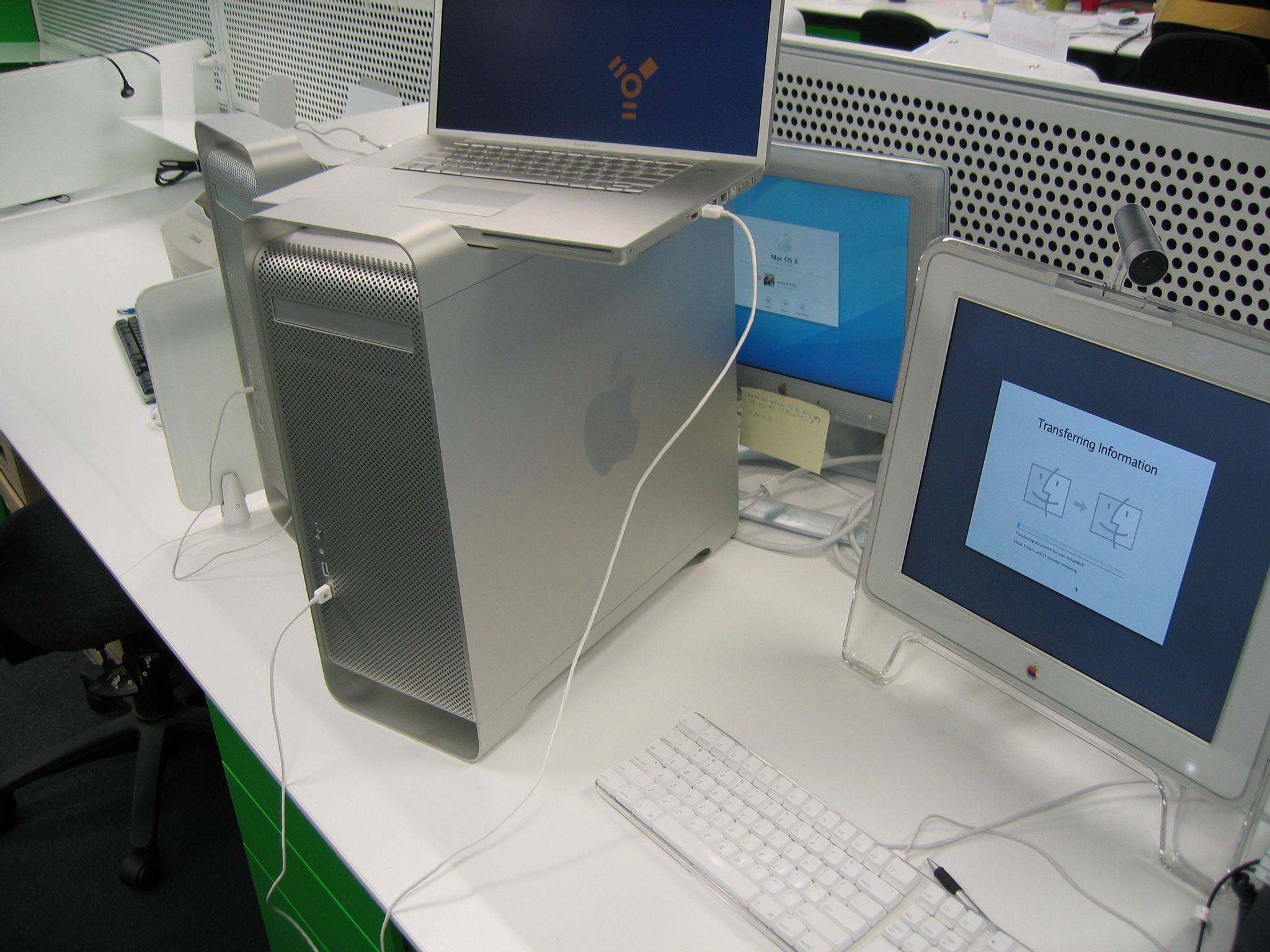 "A photo of a Quad Power Mac G5 sitting on a desk next to a monitor, with a 17"" PowerBook in Firewire Target Disk Mode on top of it."