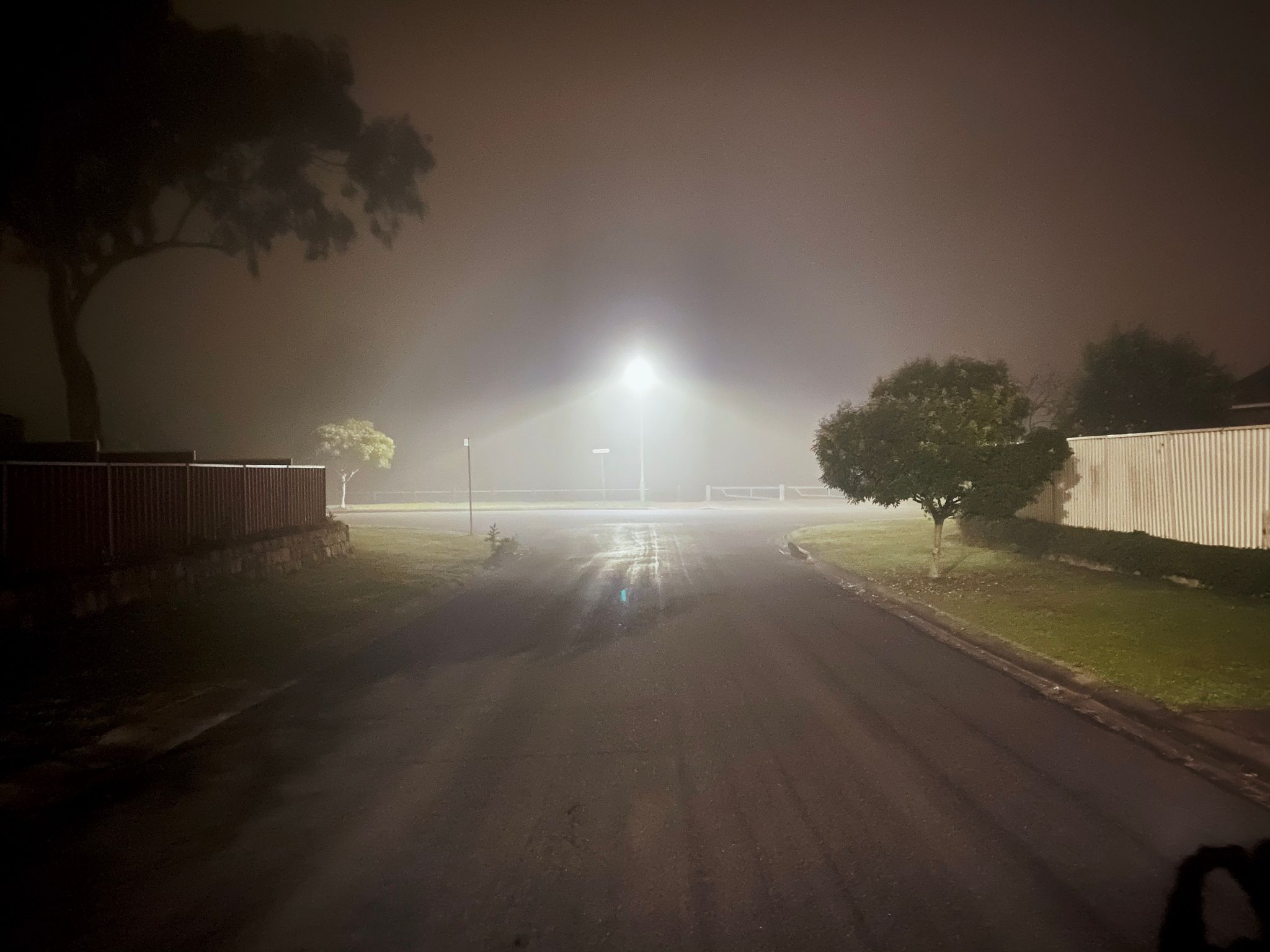 A photo taken from the middle of the road looking towards a t-intersection. A street light is at the end of the street and it's REALLY foggy.