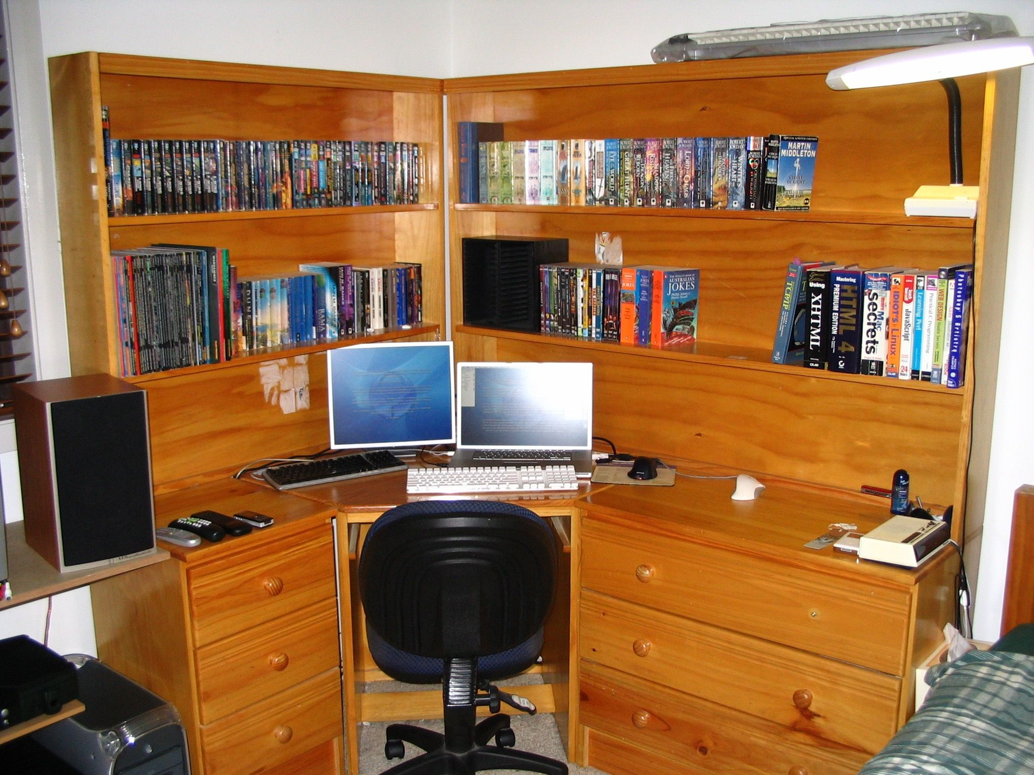 "A photo of a large wooden corner desk with built-in bookshelves sitting on top of the shelves. In the middle is a PowerBook G4 with a 17"" 4:3 display next to it and a white Apple keyboard in front, and the bookshelves are filled with books."