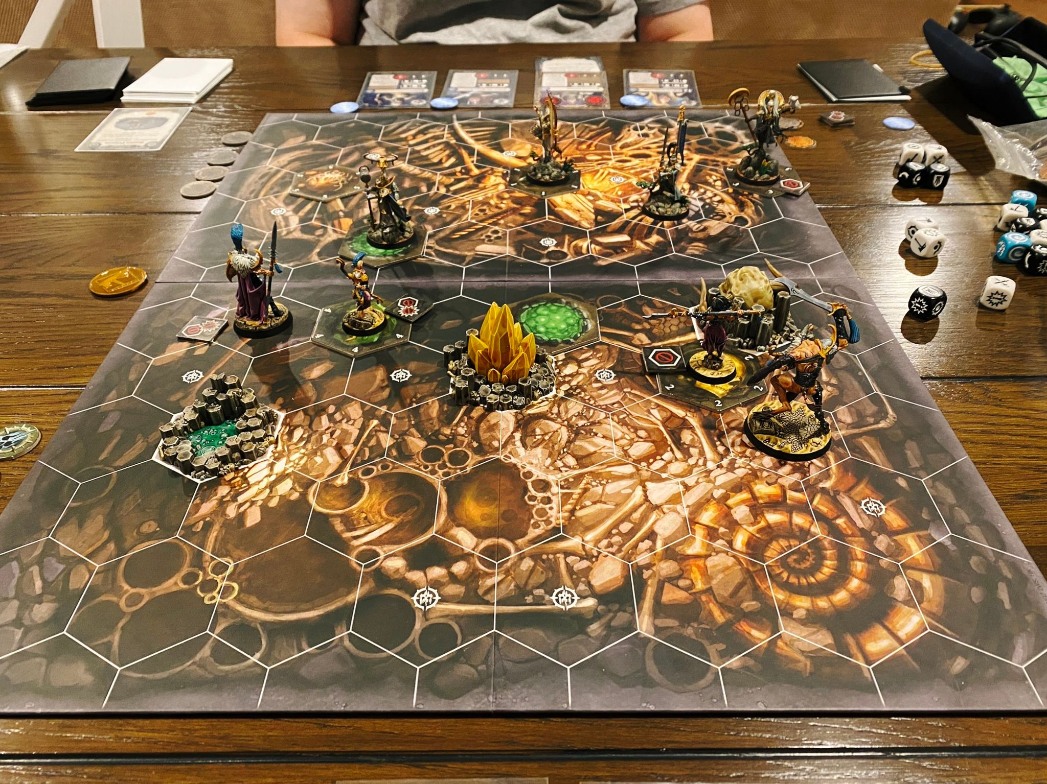 A game of Warhammer Underworlds in progress. The board has tiled hexes on it and the two warbands are lithe but armoured aelves versus Slaanesh-worshipping humans (plus a big goatman who's wielding a massive sword over his head).