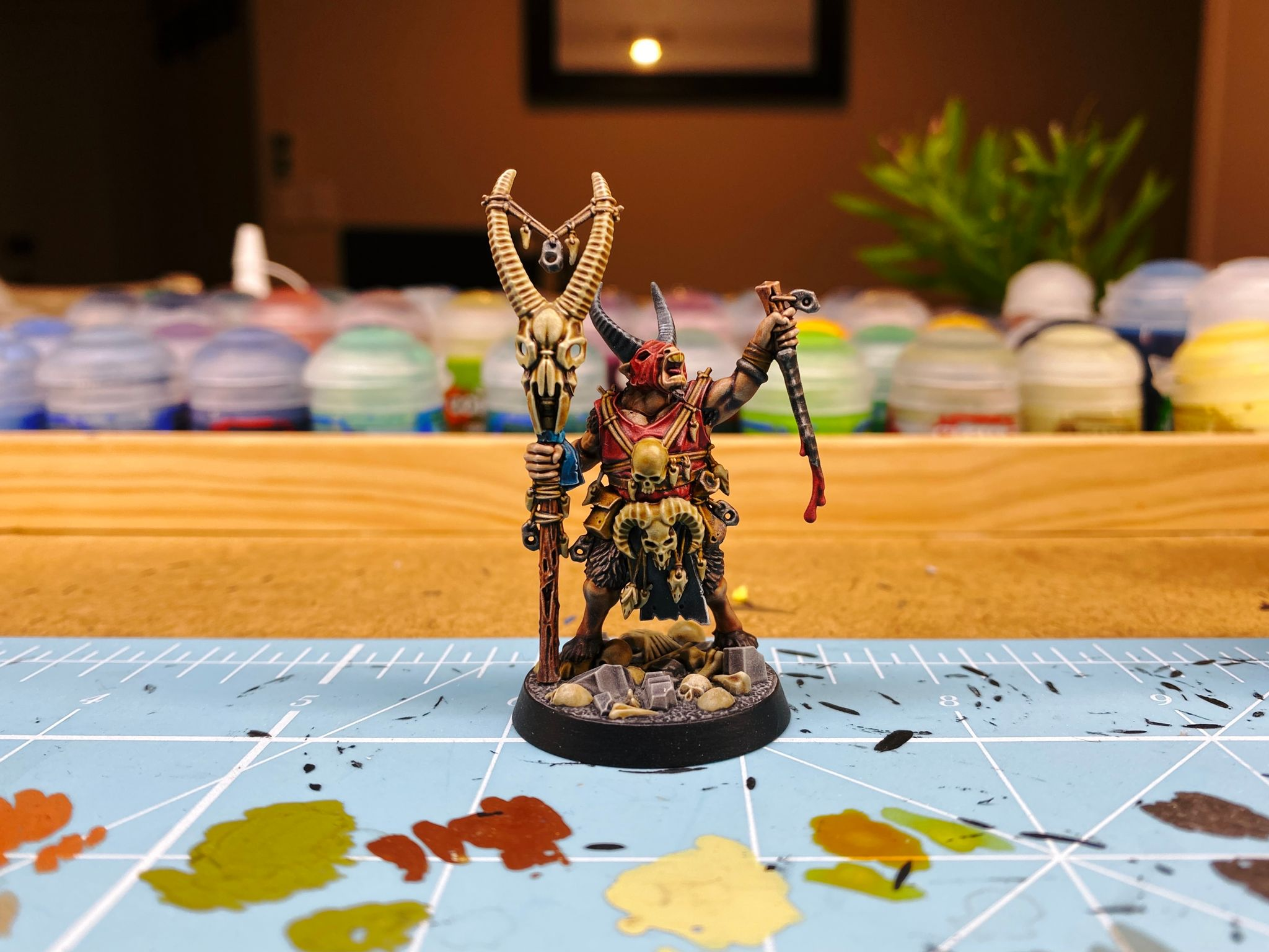 A photo of a Warhammer Underworlds: Beastgrave miniature. It's a goatman with black horns with his head tilted slightly back and mouth open like he's bellowing. He has a staff in one hand with a huge horned skull on the top, and a knife in the other that's dripping blood, and he has lots of skulls attached with string dangling from him.