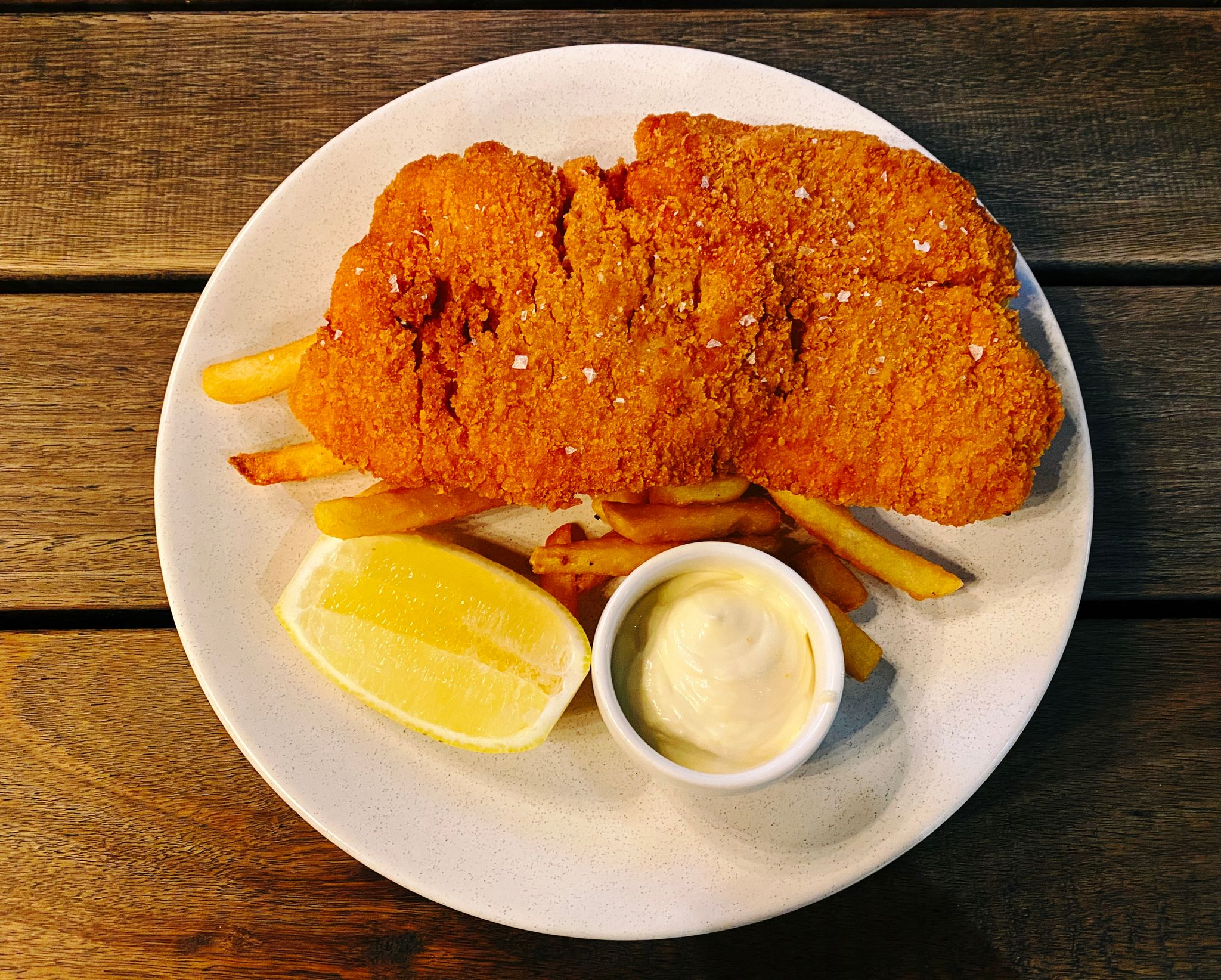 A photo of a schnitzel sitting on top of chips, with a slice of lemon and a small bowl of aioli.
