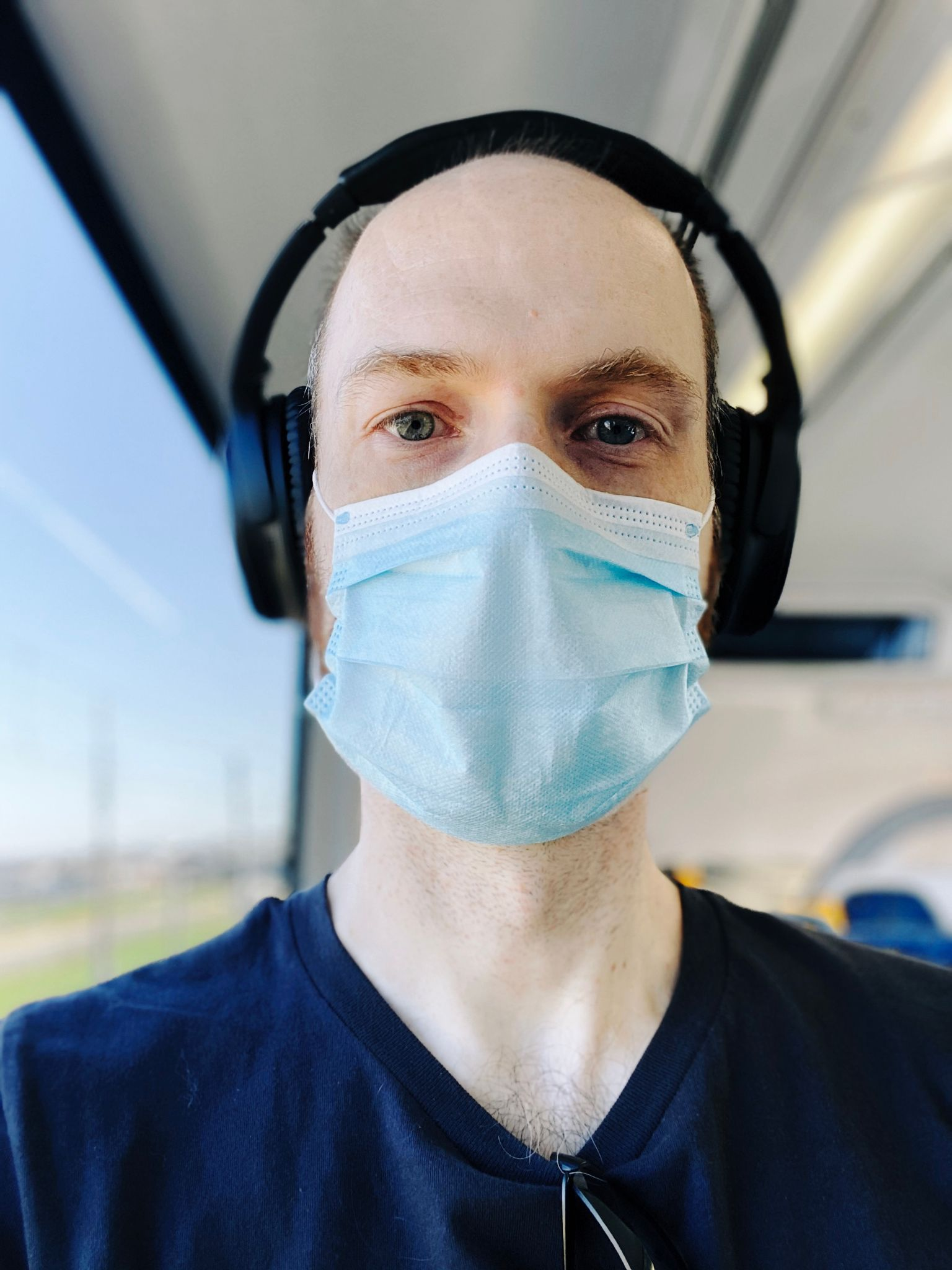 A selfie of me, a white man wearing a blue disposable mask and wearing headphones.