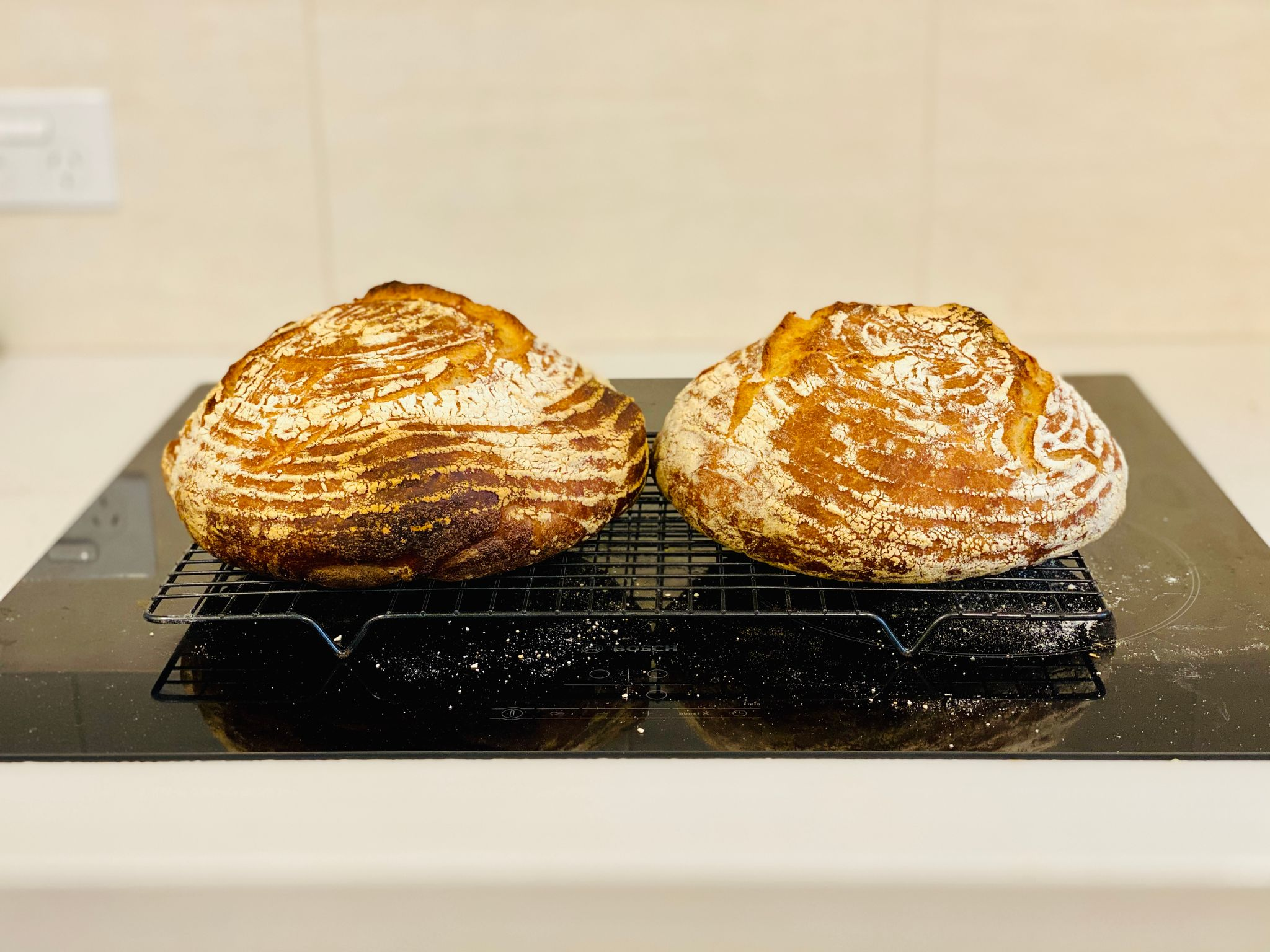 Two round golden brown loaves of bread sitting on a cooling rack.
